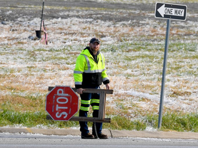 A portable stop sign is carried out and placed on Richmond Road at an intersection where the traffic lights are out in the wake of an ice storm in Staunton on Friday, Nov. 16, 2018.