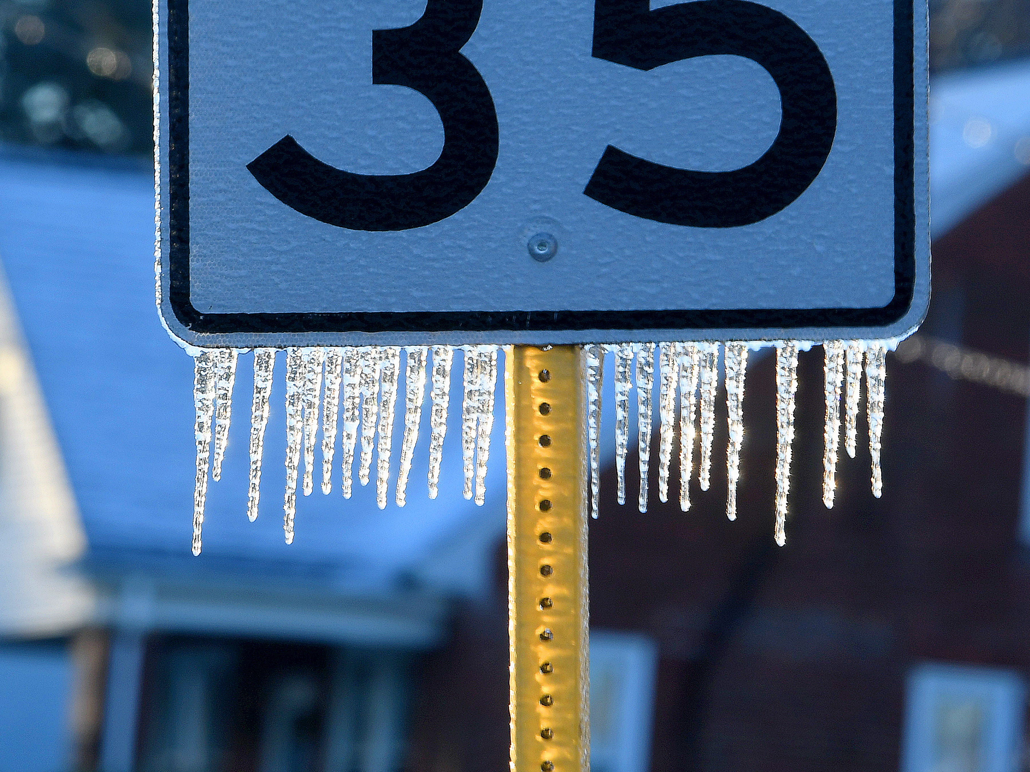 Ice covers and hangs from a speed limit sign along Barterbrook Road on an ice-covered Friday morning, Nov. 16, 2018.