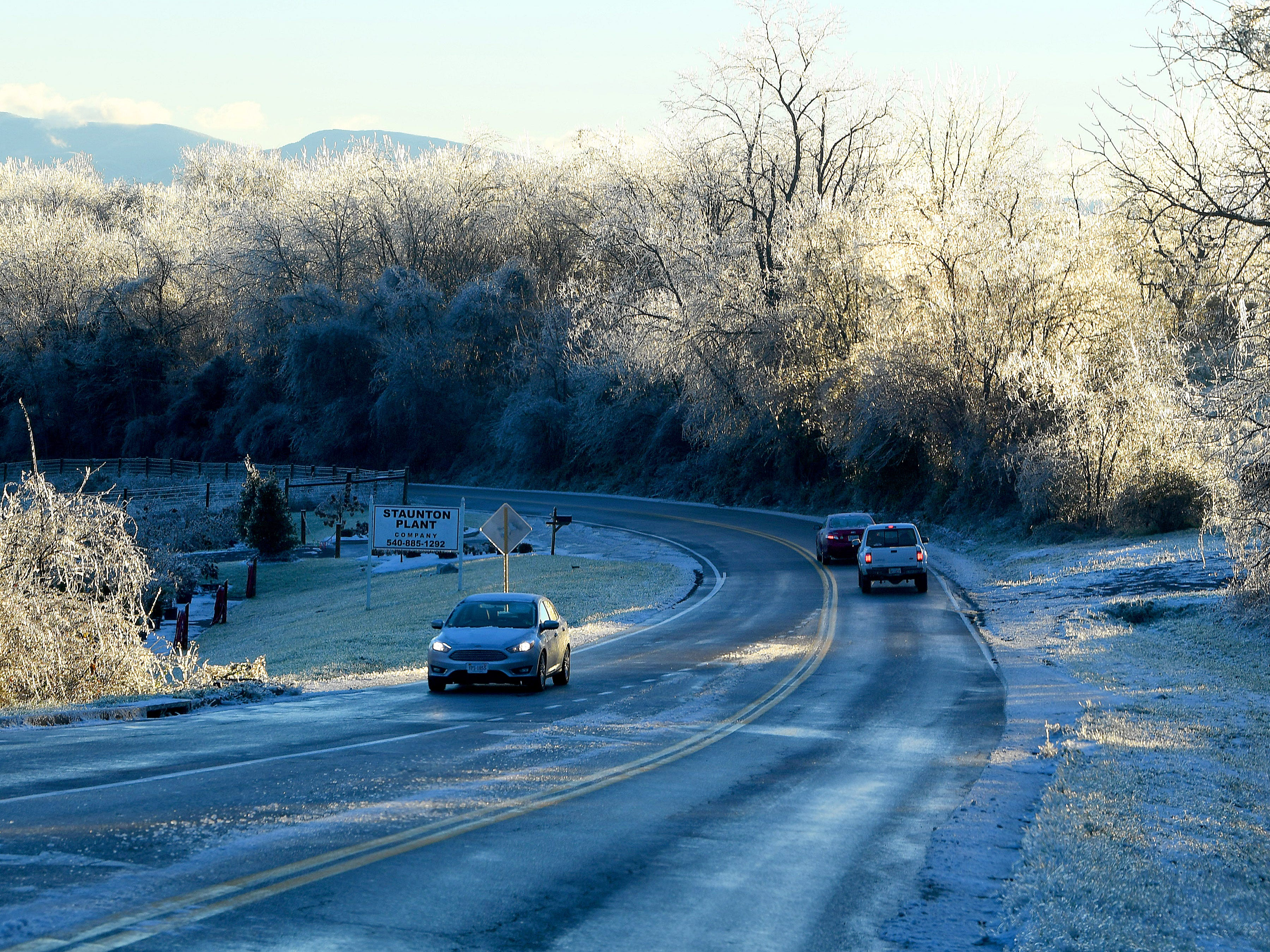 Sunlight gives ice on trees a whitish glow in the backdrop as traffic moves along Frontier Drive in Staunton on an ice-covered Friday morning, Nov. 16, 2018.