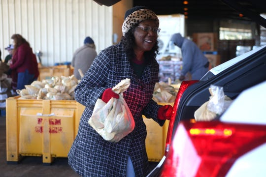 A volunteer loads bags of food into a trunk as Farm Share provides roughly 1,000 meals for families in Quincy around Thanksgiving. Farm Share is offering food the those hurt by the government shutdown.