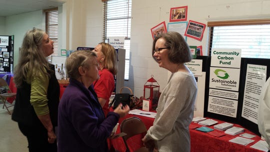 Debbie Gibson, left, and Pamela McVety with visitors at the Alternative Christmas Market Carbon Fund booth.