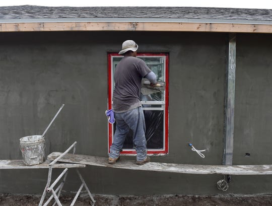 Stucco mason Eric Cardona applies a layer of stucco around a window frame of a home under construction by builder Homecrete Homes, of Port St. Lucie, at the 1500 block of Andalusia Road on Thursday, Nov. 15, 2018, in Port St. Lucie. Builders are experiencing cost increases in materials and labor because of higher demand caused by un uptick in construction.