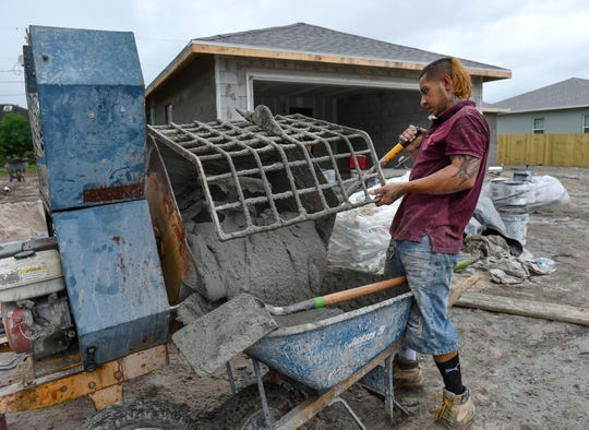 Construction worker Carlos Roberto retrieves a fresh mix of stucco to coat the outside of a home being built by Homecrete Homes, of Port St. Lucie, in the 1500 block of Andalusia Road on Thursday, Nov. 15, 2018, in Port St. Lucie. Builders are experiencing cost increases in materials and labor because of shortages.