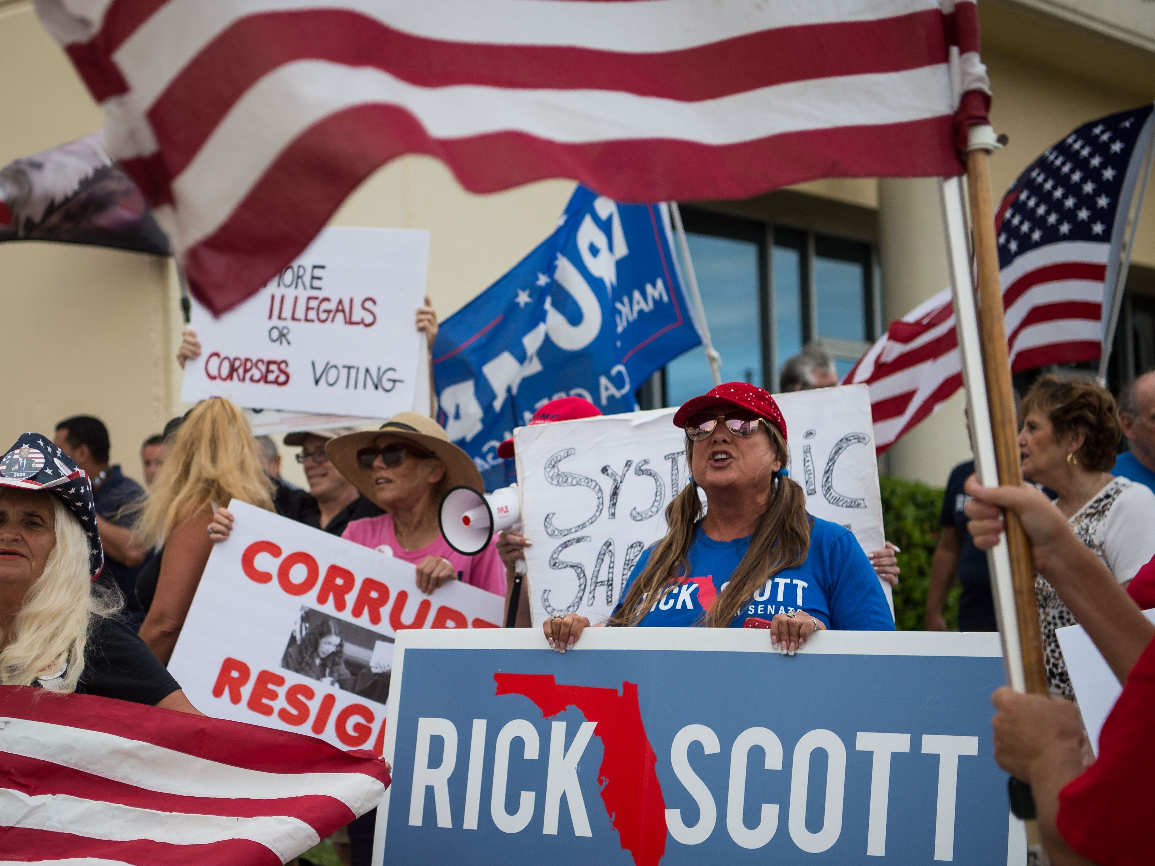 Hilary Sue (right), of Stuart, a poll watcher for several counties, holds a Rick Scott for Senate campaign sign outside the Palm Beach County Supervisor of Elections Service Center in Riviera Beach on Thursday, Nov. 15, 2018, as the recount continues inside under Supervisor of Elections Susan Bucher.
