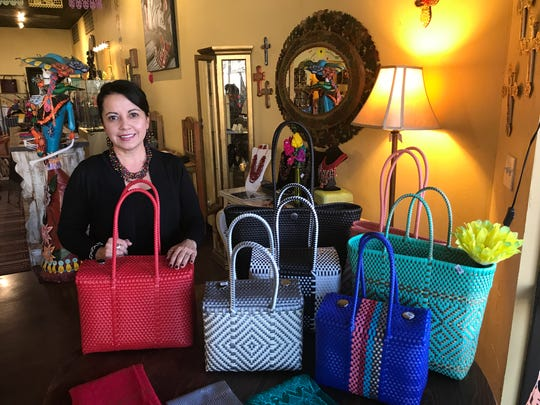 Desert Gypsy manager JoAnne Bustamante shows an array of popular purses for women, great holiday gift ideas.