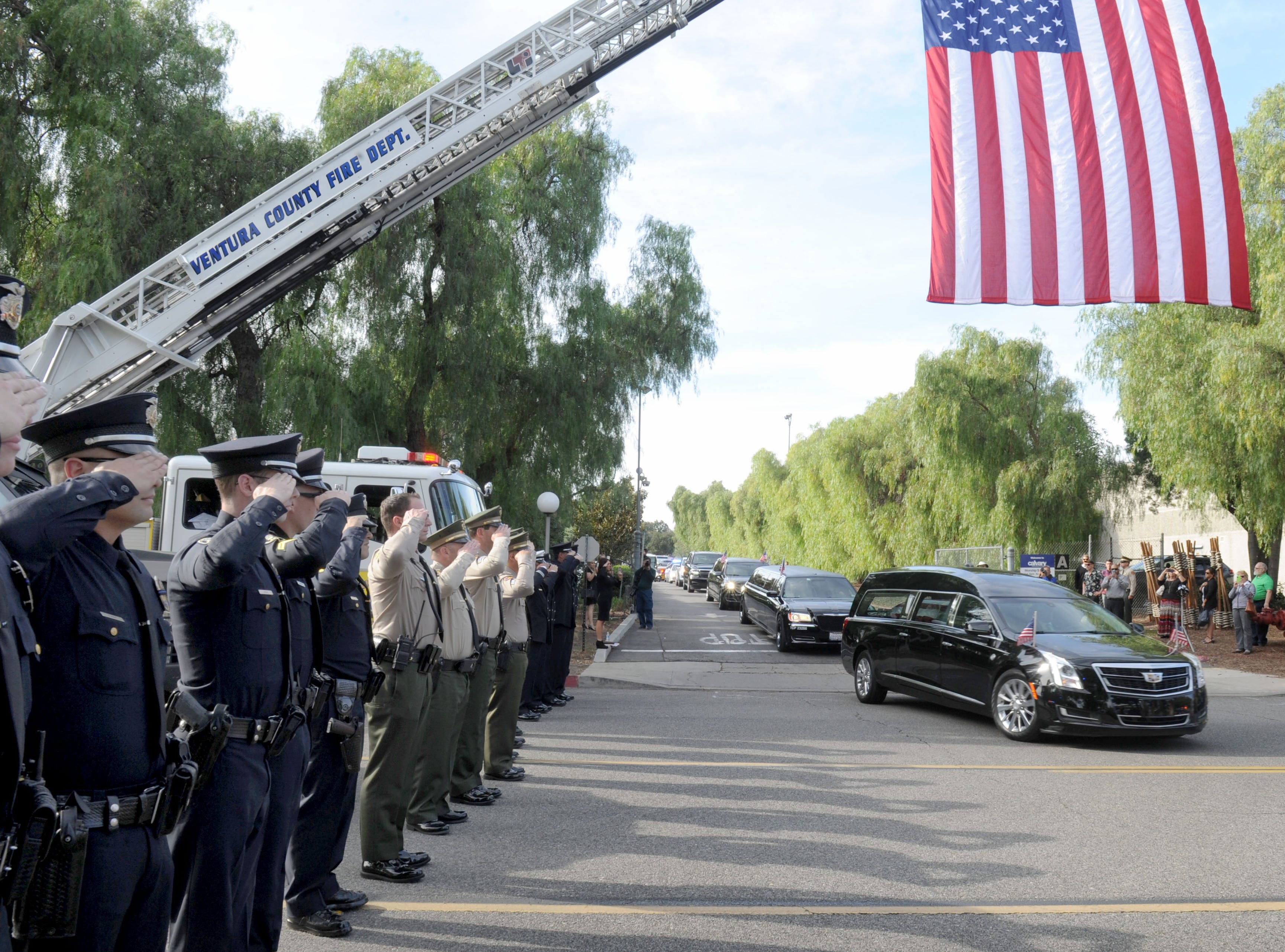 Law enforcement personnel salute as the hearse carrying Ventura County Sheriff's Office Sgt. Ron Helus drives from his  memorial service at the Calvary Community Church on Thursday. He was buried at Pierce Brothers Valley Oaks Memorial Park on Lindero Canyon Road.