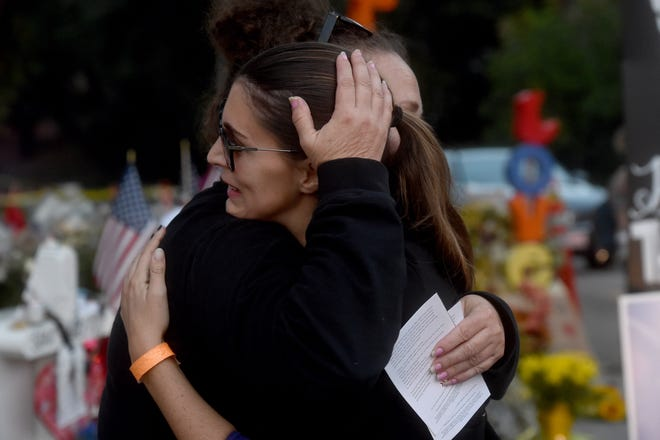 Margot Marty, of Thousand Oaks, shares a hug with a woman after writing a message on the sidewalk for Kristina Morisette, who was among those who died in the Nov. 7 shooting at the Borderline Bar & Grill.