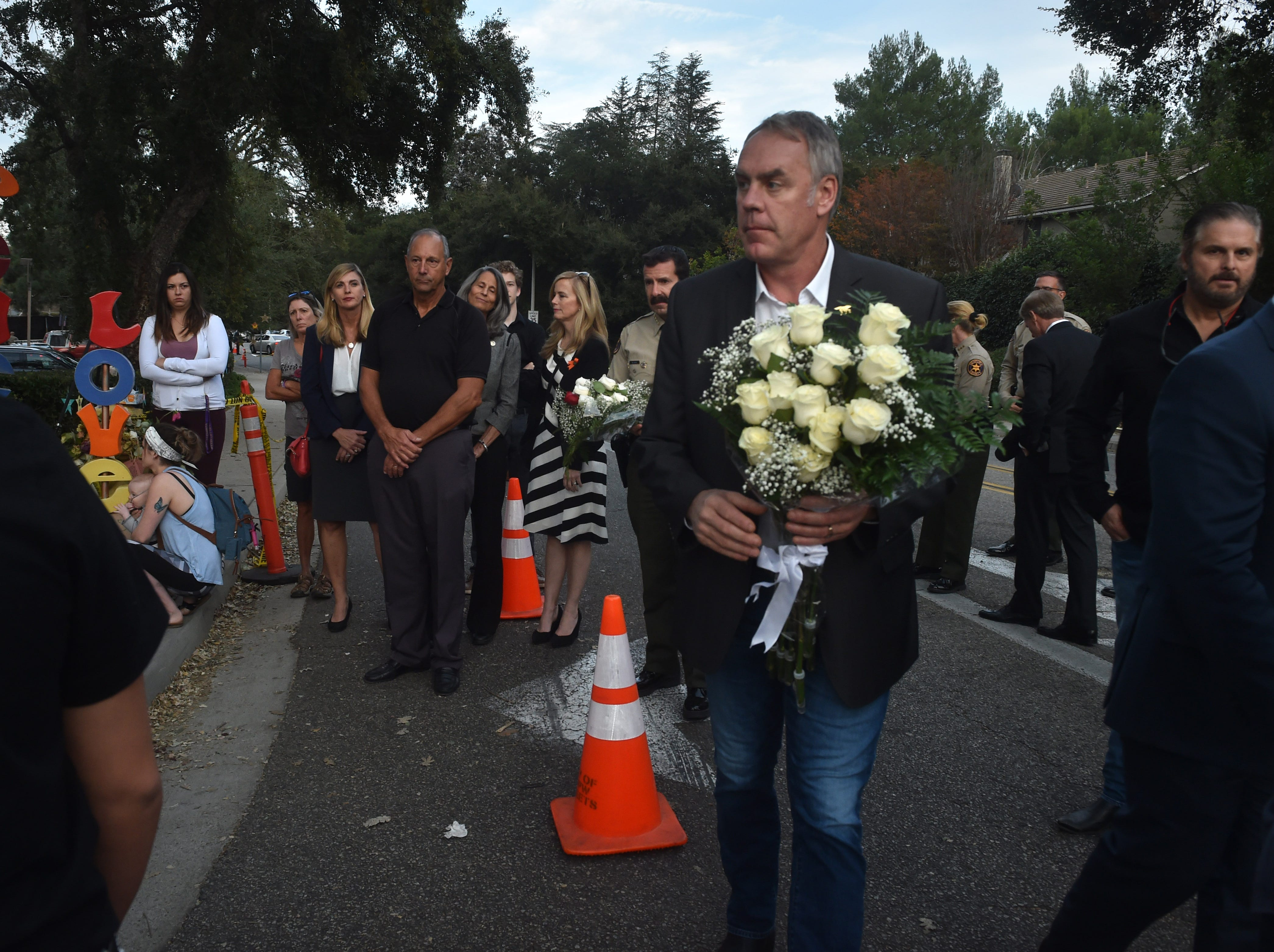 U.S. Interior Secretary Ryan Zinke on Thursday delivers flowers to a memorial wall near the Borderline Bar & Grill in Thousand Oaks, where 12 people were killed by a gunman who then turned the gun on himself Nov. 7. Zinke was in Ventura County to see the damage caused by the Woolsey and Hill fires, which started the day after the shootings.