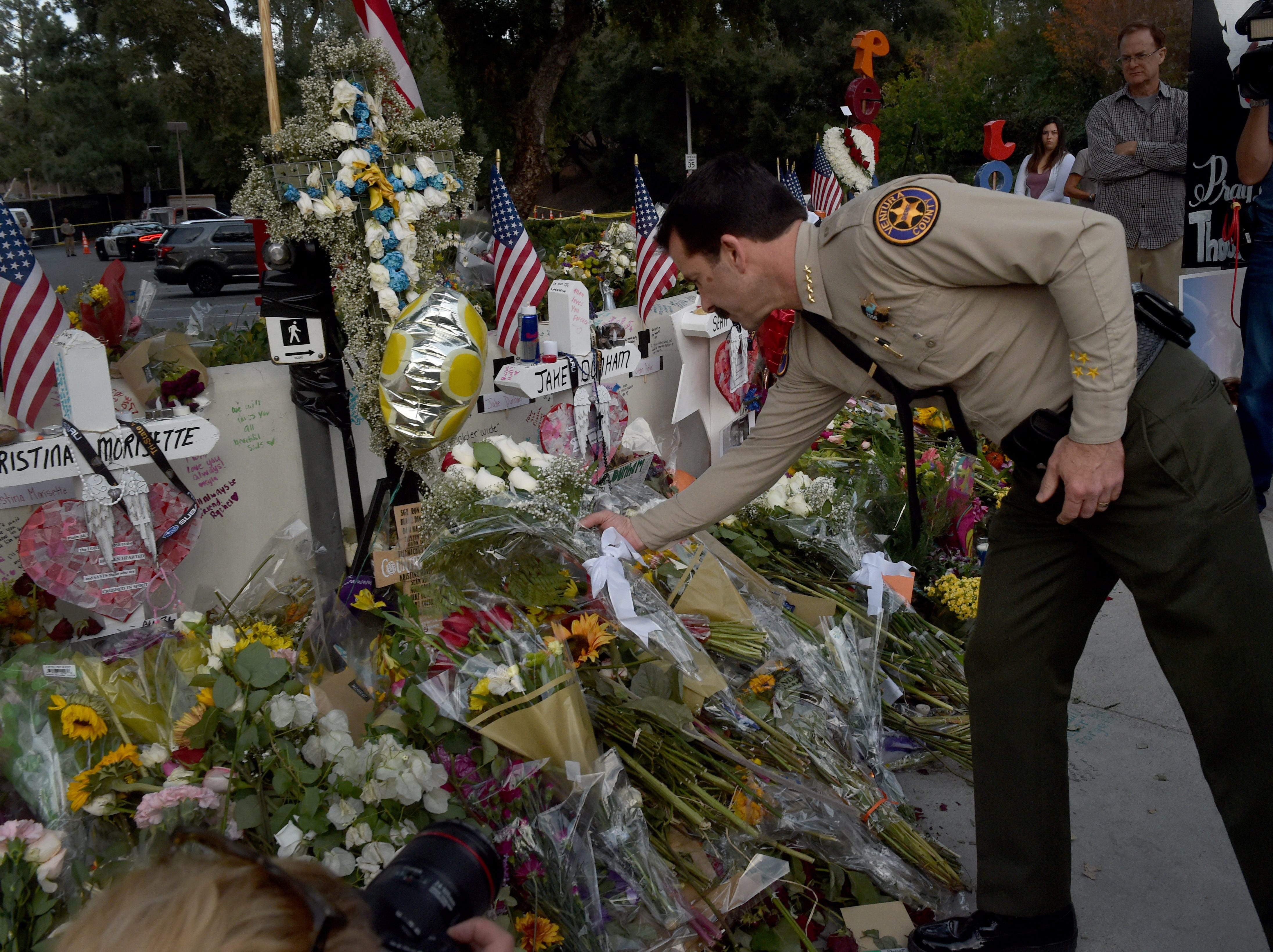 Ventura County Sheriff Bill Ayub places flowers Thursday on a memorial wall near the Borderline Bar & Grill in Thousand Oaks, where 12 people were killed Nov. 7. One of those slain was sheriff's Sgt. Ron Helus.