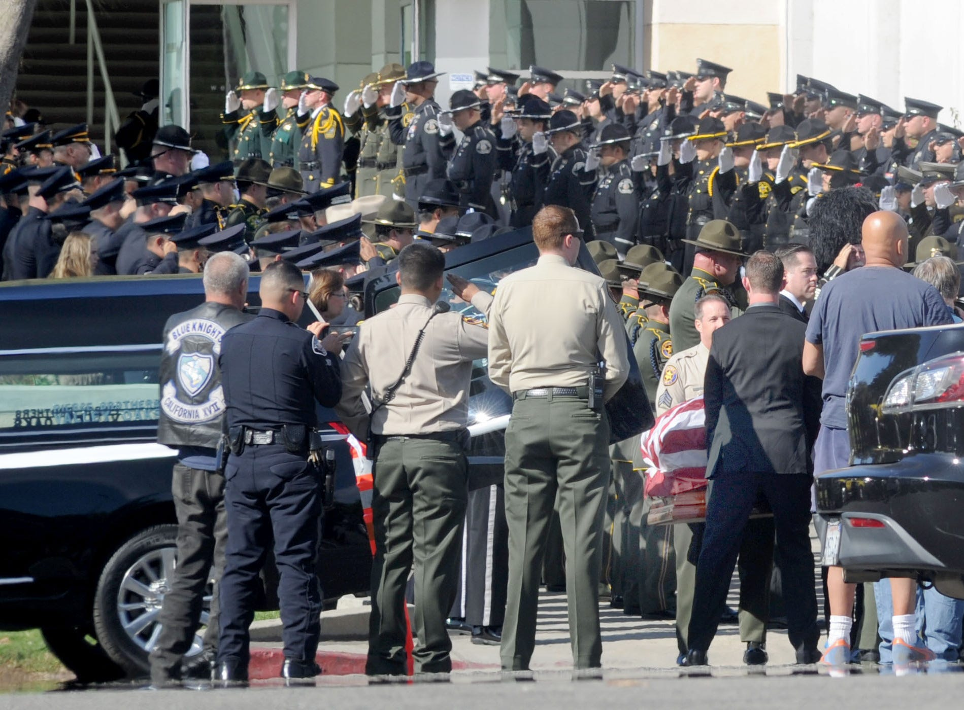 Law enforcement personnel salute as the casket of Ventura County Sheriff's Office Sgt. Ron Helus is carried out after his memorial service at Calvary Community Church Thursday. He was buried at Pierce Brothers Valley Oaks Memorial Park on Lindero Canyon Road.