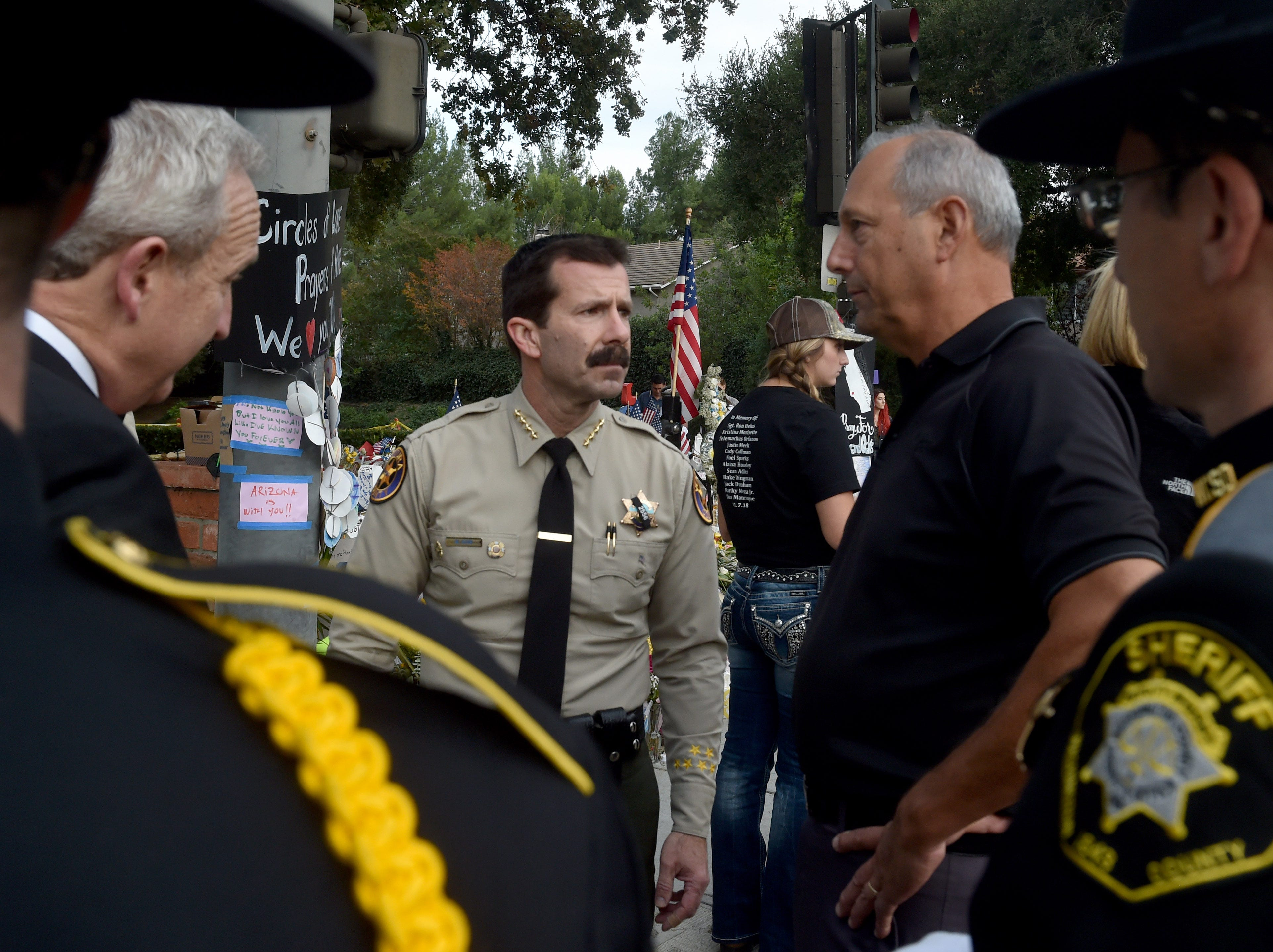 Ventura County Sheriff Bill Ayub speaks with Navy Capt. Roger Meek at a memorial wall near the Borderline Bar & Grill in Thousand Oaks, where 12 people were killed Nov. 7. Meek's son Justin Meek was among the victims.