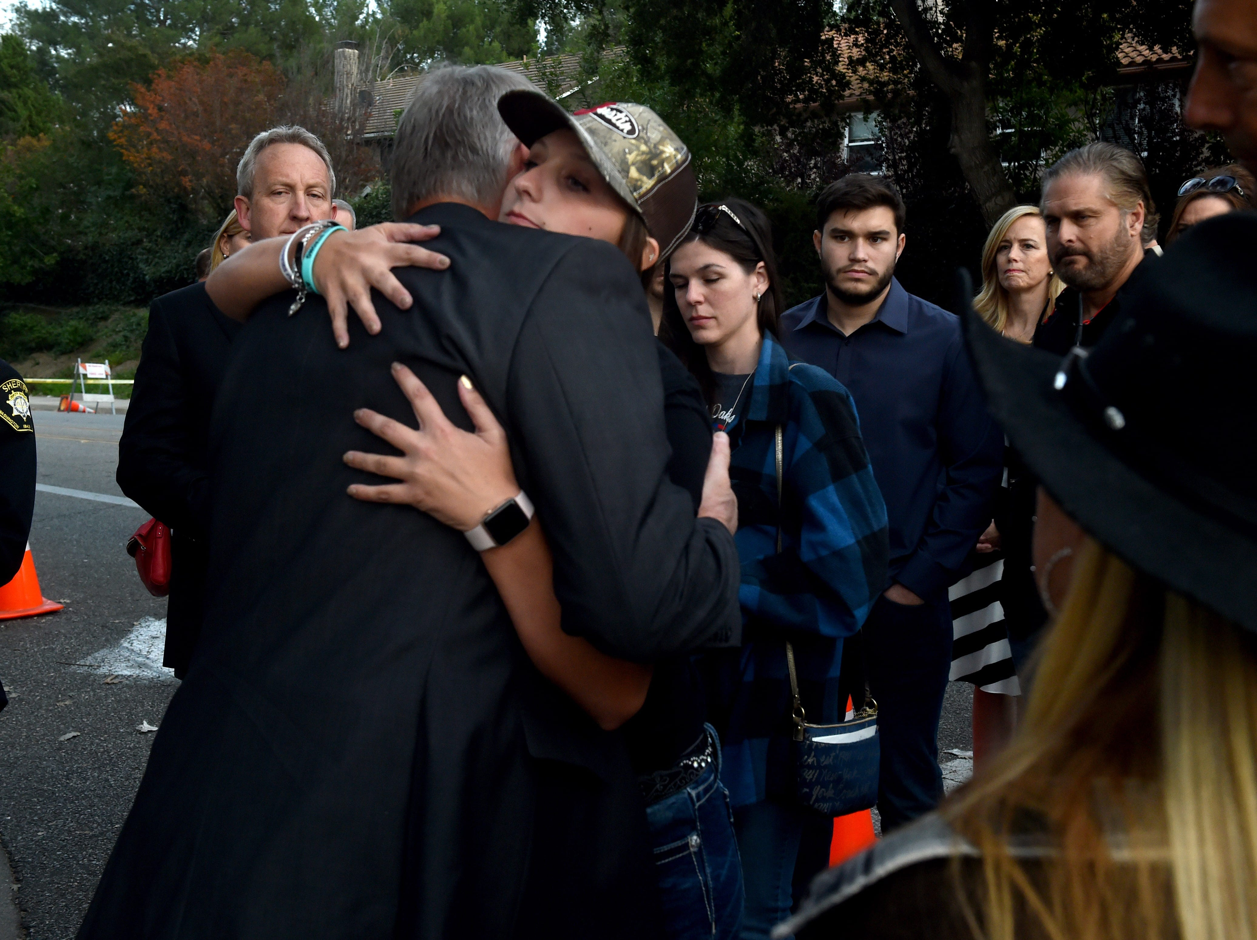 Victoria Rose Mee, whose brother Justin Meek was among those who died in the Nov. 7 shooting at the Borderline Bar & Grill in Thousand Oaks, shares a hug Thursday with U.S. Interior Secretary Ryan Zinke at a memorial wall near the bar.