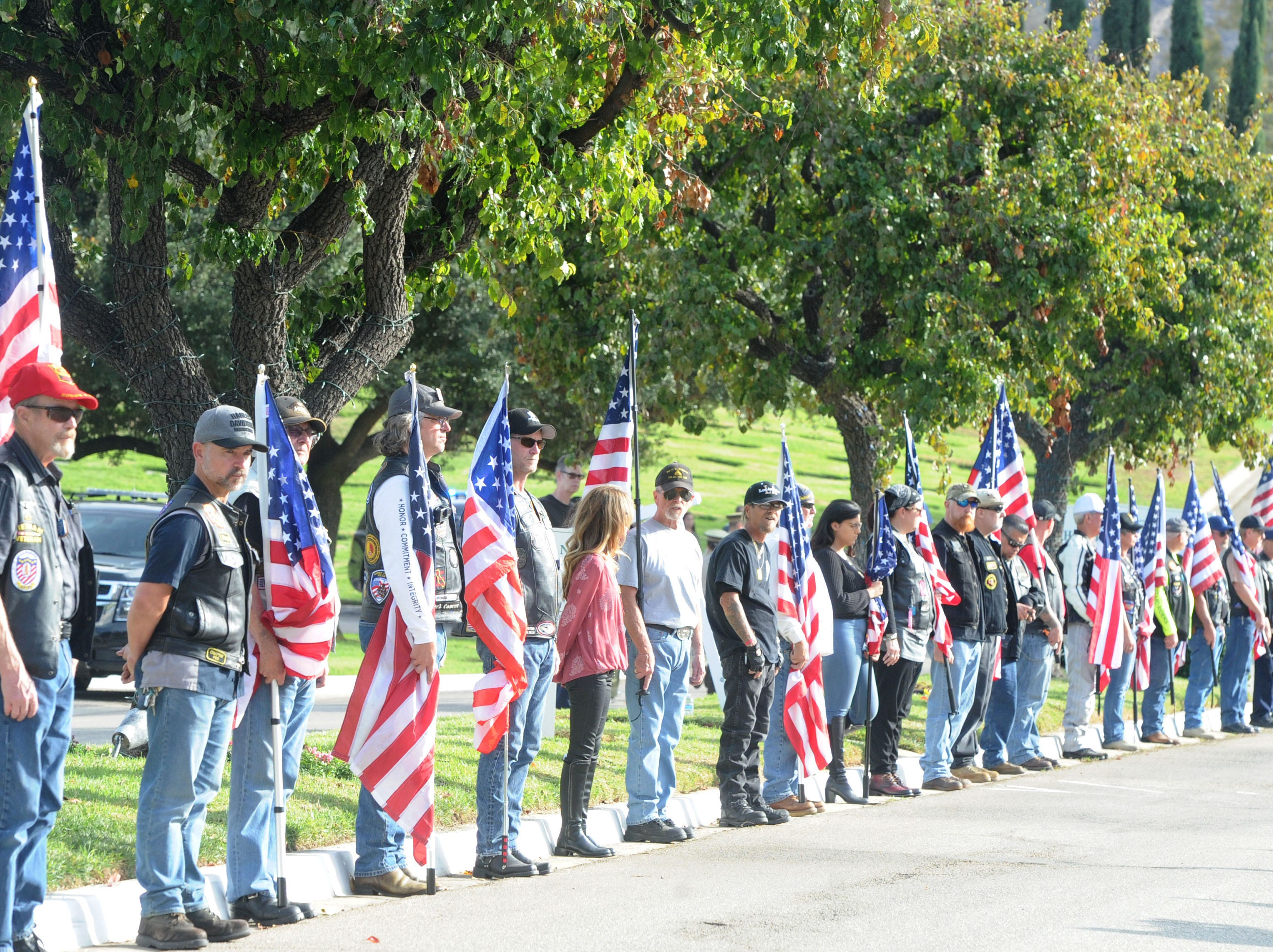 A group of people line up with flags to the entrance of Pierce Brothers Valley Oaks Memorial Park Thursday where Ventura County Sheriff's Office Sgt. Ron Helus was to be buried.