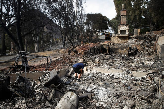 Roger Kelton searches through the remains of his mother-in-law's home leveled by the Woolsey Fire on Tuesday in Agoura Hills.