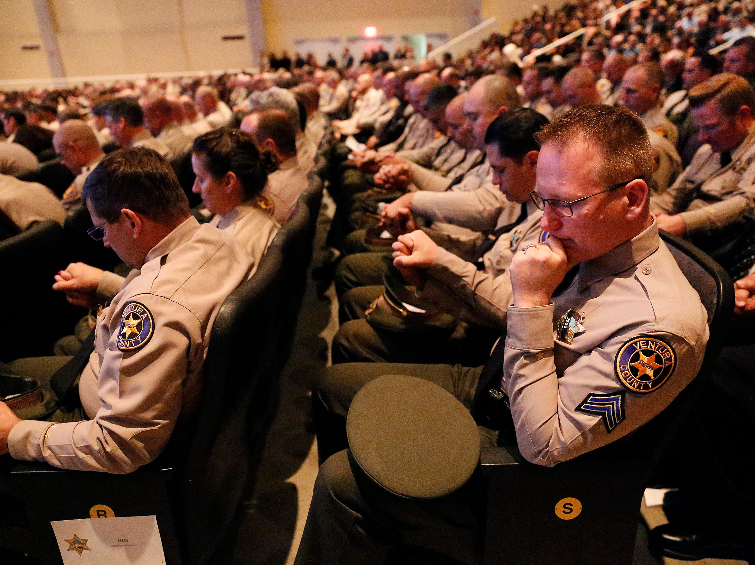 Deputy Dan McLaughlin, right, holds hands with other deputies during a closing prayer of the memorial service for Ventura County Sheriff's Office Sgt. Ron Helus at Calvary Community Church in Westlake Village on Thursday.