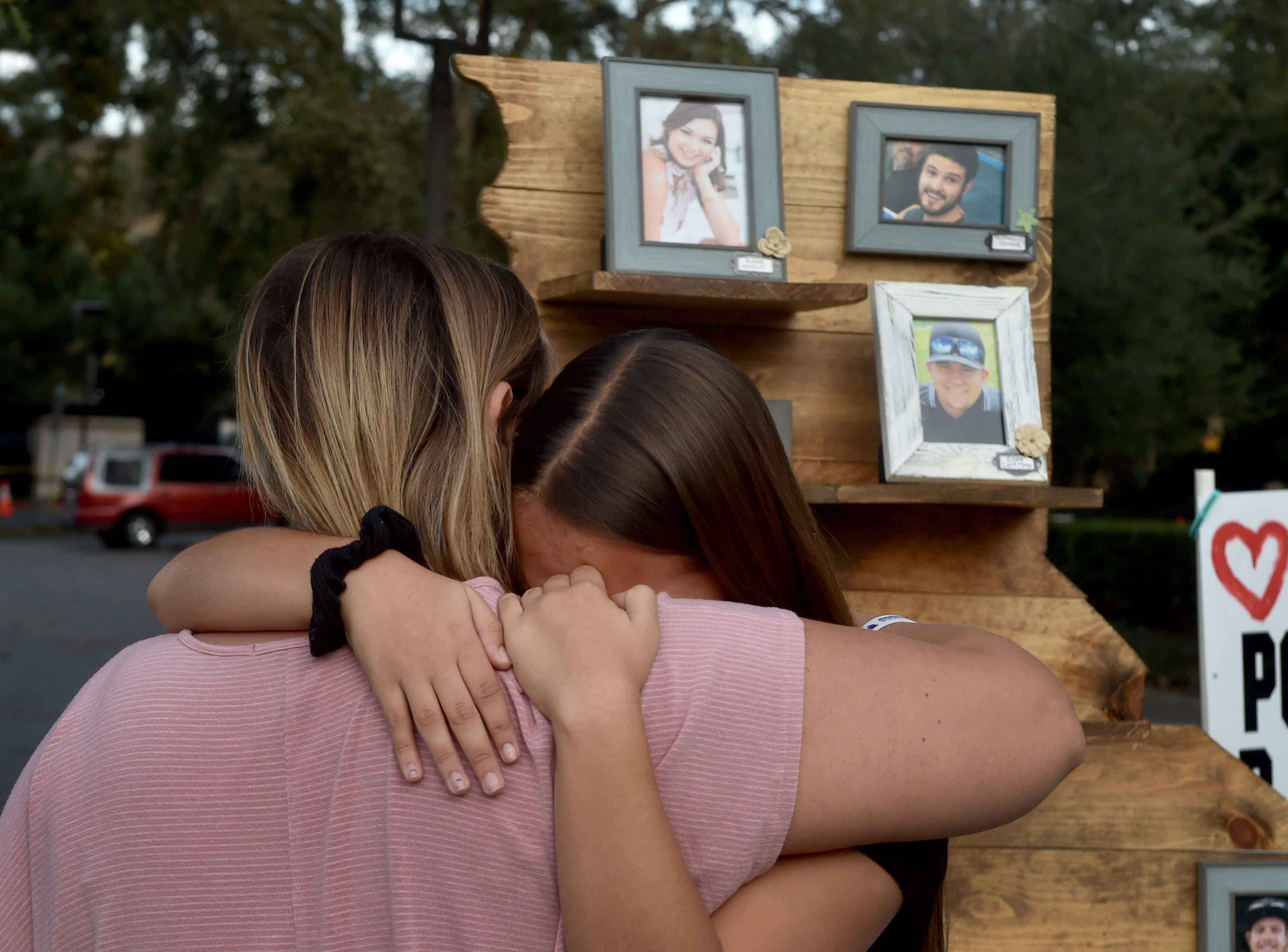 Mia Carlton, of Simi Valley, gets a hug from her mother on Thursday after placing a photo of her cousin Cody Gifford-Coffman on a display at a memorial wall near the Borderline Bar & Grill in Thousand Oaks, where he was killed Nov. 7.