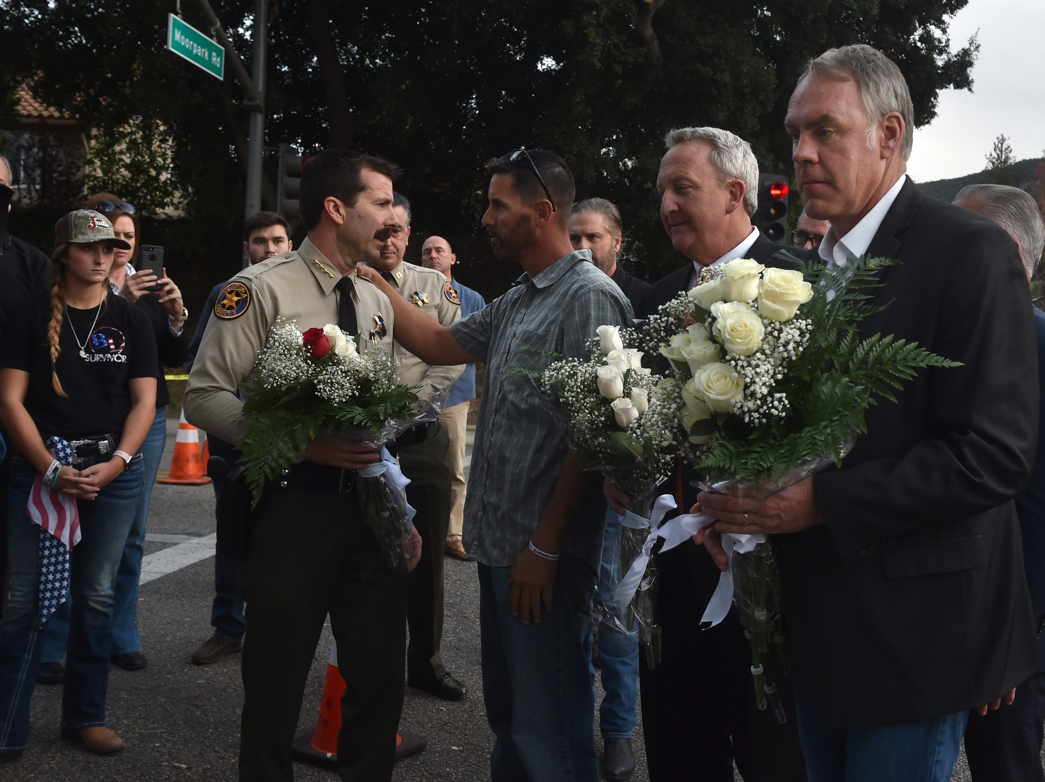 U.S. Interior Secretary Ryan Zinke, right, and Ventura County Sheriff Bill Ayub deliver flowers Thursday to a memorial wall near the Borderline Bar & Grill in Thousand Oaks, where 12 people were killed by a gunman who then turned the gun on himself Nov. 7. Zinke was in Ventura County to see the damage caused by the Woolsey and Hill fires, which started the day after the shootings. His visit coincided with the funeral of sheriff's Sgt. Ron Helus, one one those killed by the gunman.