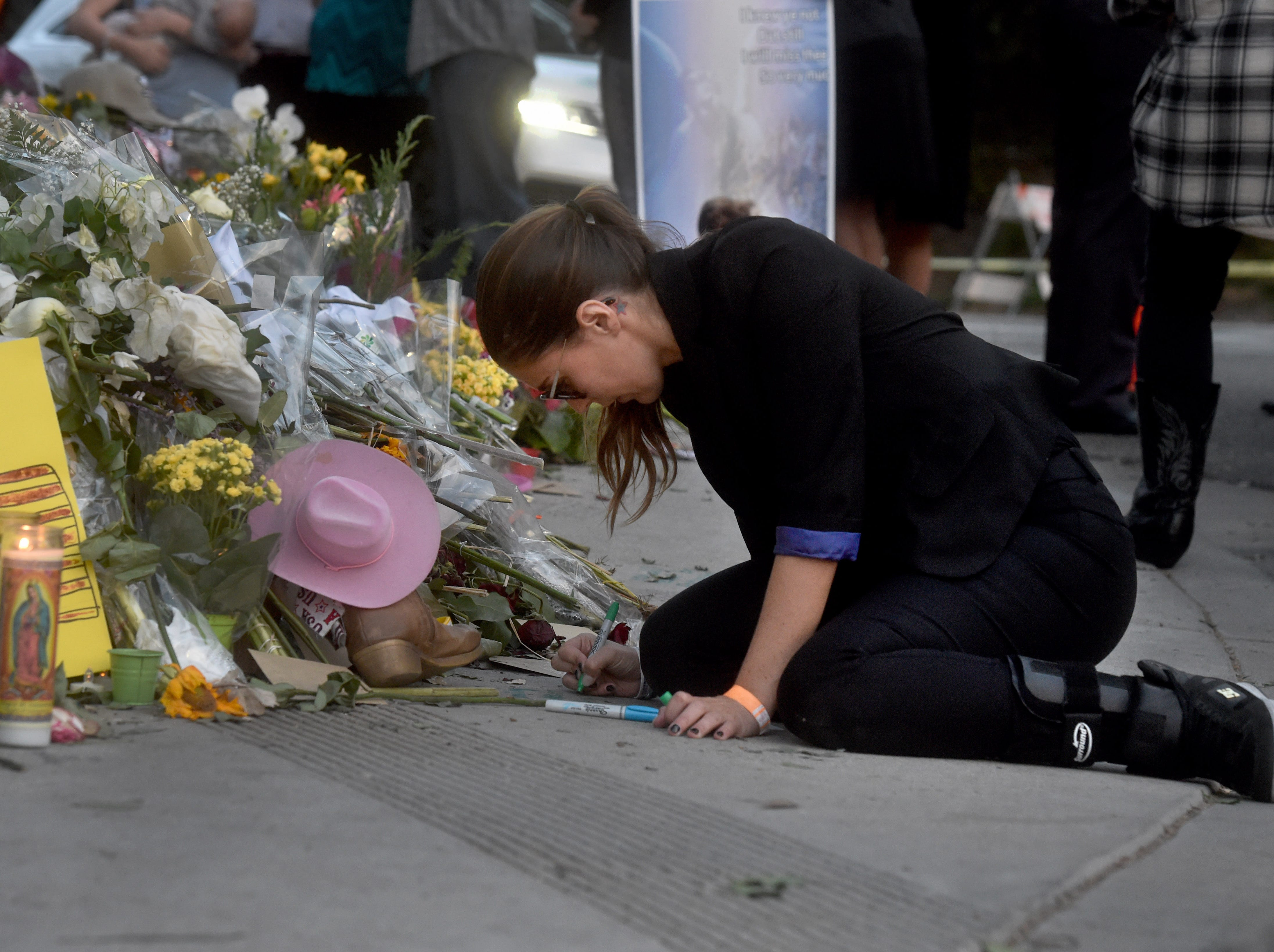 Margot Marty, of Thousand Oaks, writes a message on the sidewalk for Kristina Morisette, who was among those who died in the Nov. 7 shooting at the Borderline Bar & Grill.