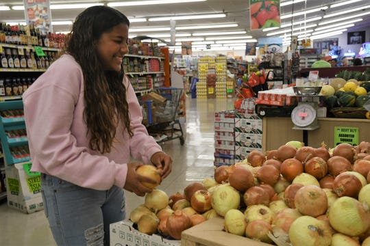 Adrina Cole picks an onion at Best Buy Market. She's looking forward to helping her family prepare this year's Thanksgiving dinner after completing a school baking class.