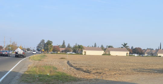 Traffic moves east on Prosperity Avenue pass an empty lot next to Evolutions. The Tulare hospital board approved the sale of the property seeking to raise funds.