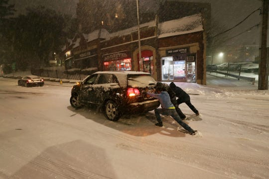 Good samaritans help to push a driver stuck on a snow covered Westchester Avenue by Armory Place in White Plains during a steady snowfall Nov. 15, 2018.