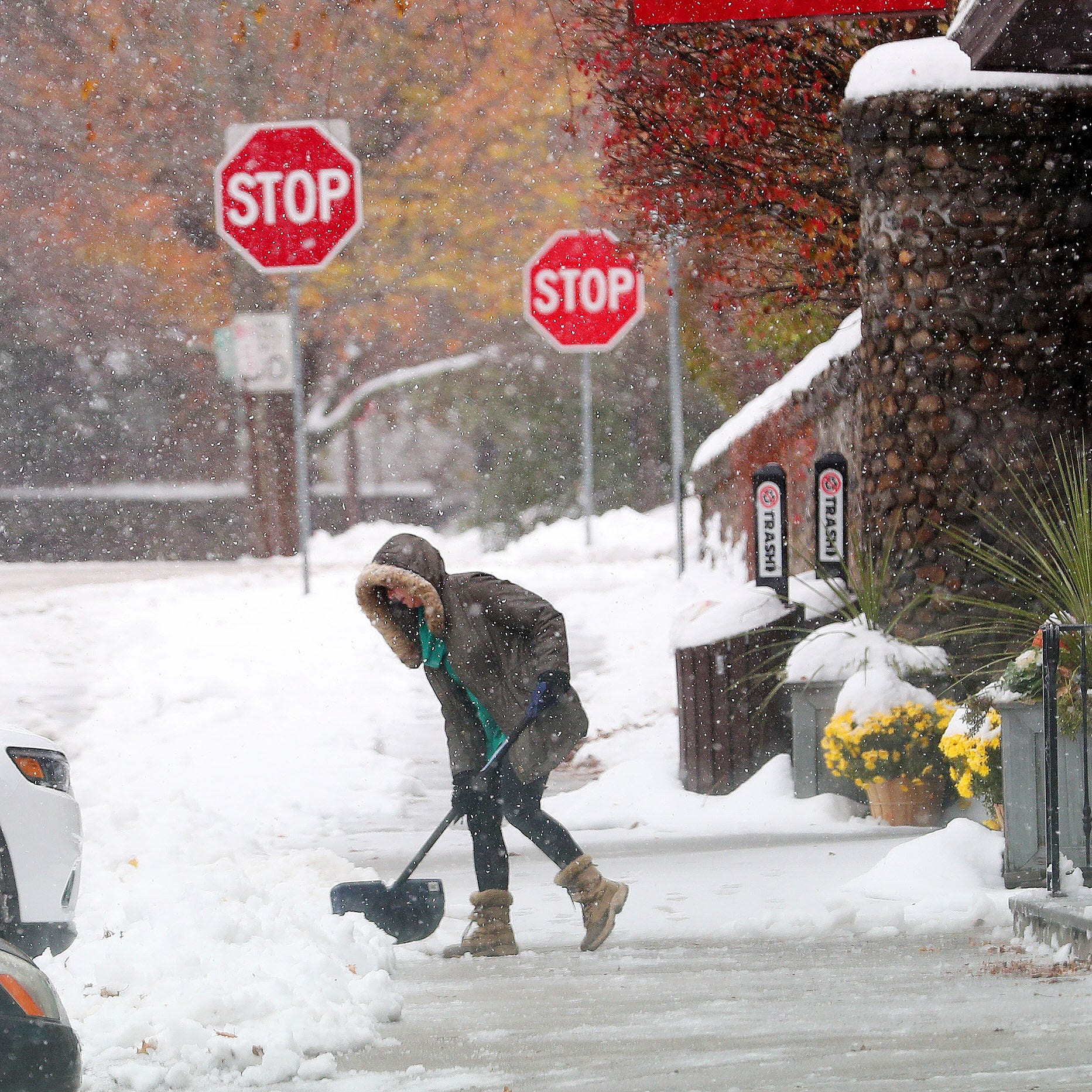 A store owner shovels the sidewalk outside her business on the Parkway in Katonah Nov. 16, 2018.