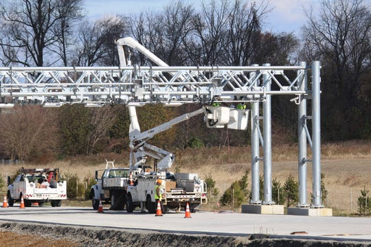 Workers install in new electronic tolling system that will keep motorists traveling the 15-mile toll road form having the option to pay with cash as All Electronic Tolling (AET) will be used for the first time in Delaware to collect tolls.
