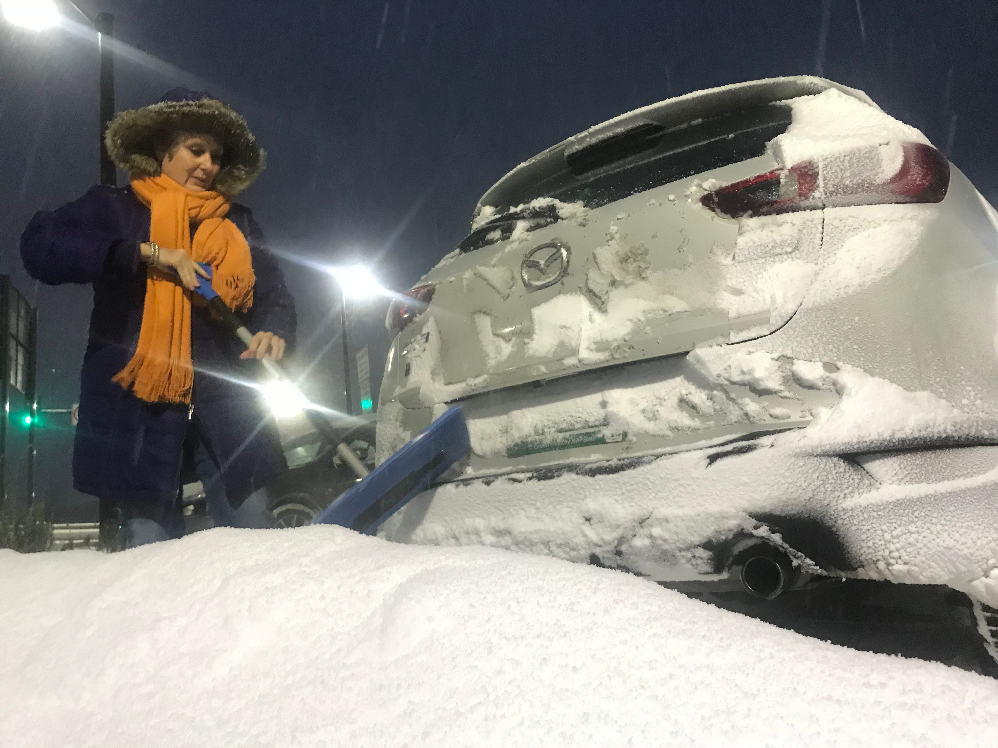 Gwen Genno of Essex, Vermont, takes a moment to clear snow from her car at the Richmond Park and Ride, Nov. 16, 2018, as a winter storm settled into Vermont, promising upwards of a foot of snow in some areas.
