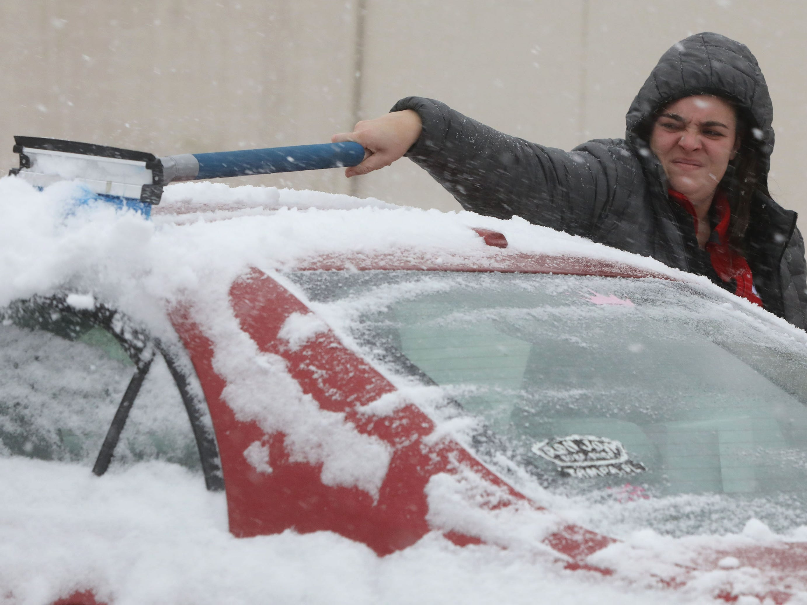 Kassie Mattoon clears snow from her car as she heads home from work in Totowa, N.J.
