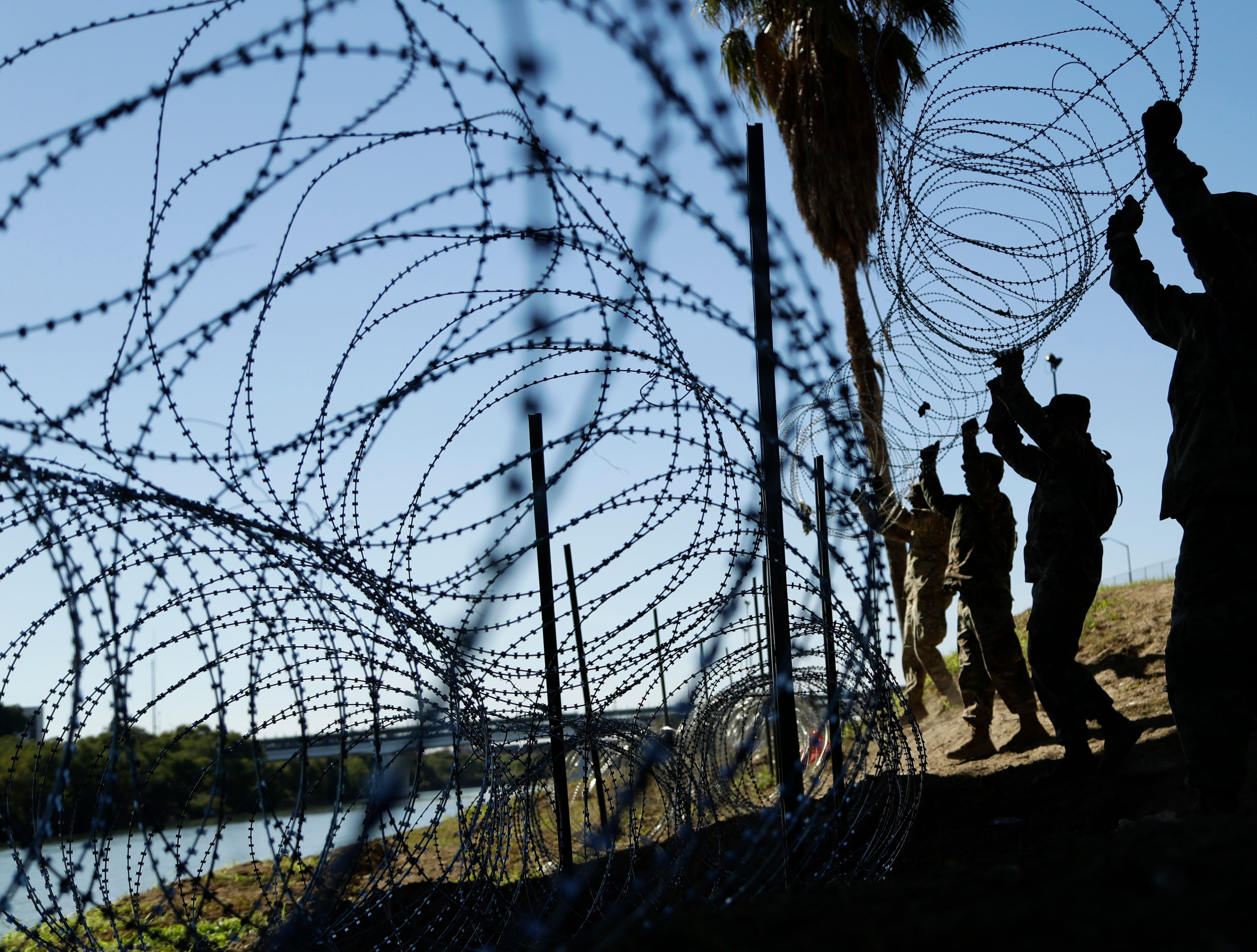 Members of the U.S. military install multiple tiers of concertina wire along the banks of the Rio Grande near the Juarez-Lincoln Bridge at the U.S.-Mexico border, Friday, Nov. 16, 2018, in Laredo, Texas.