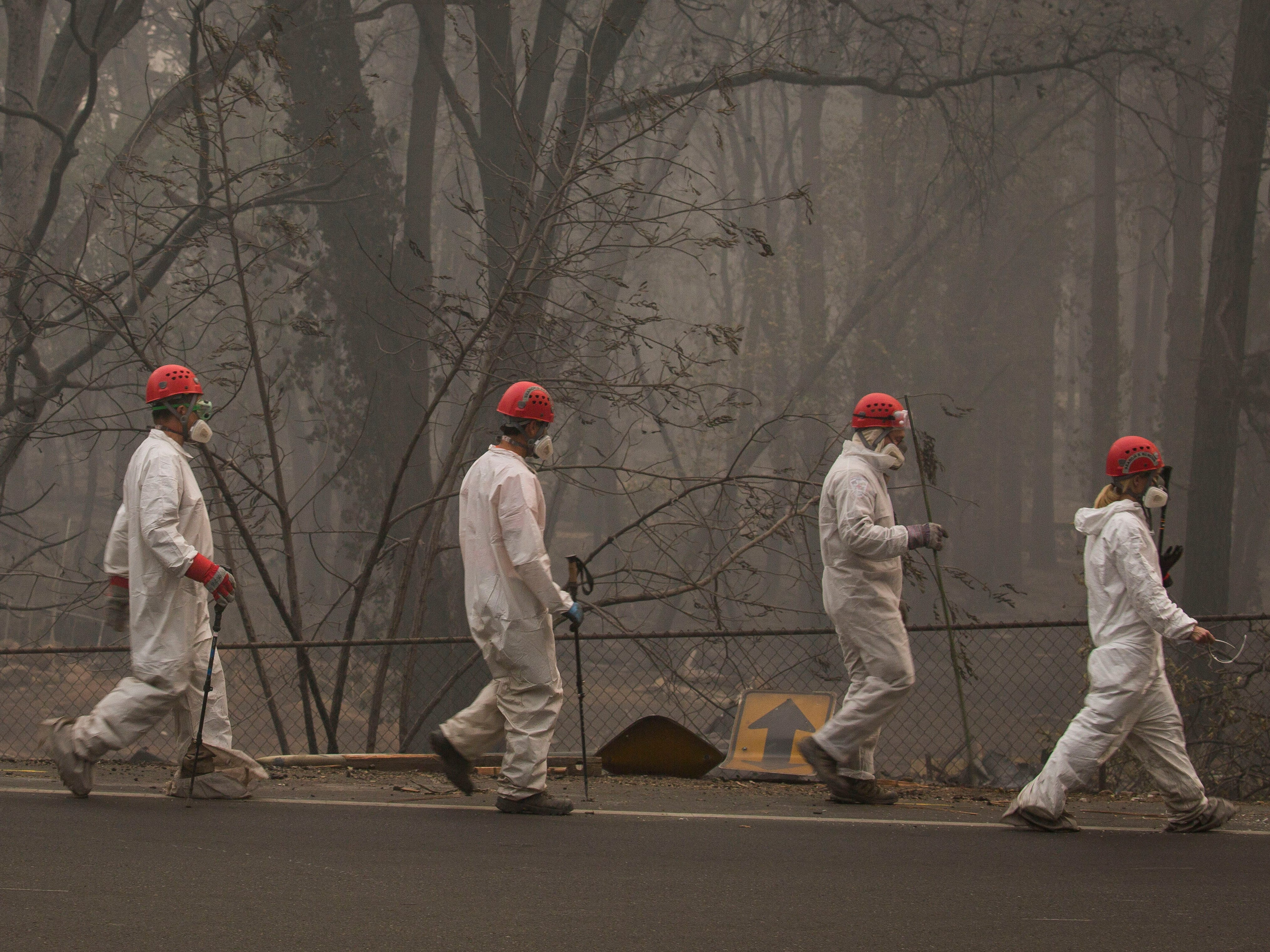 Search and rescue personnel walk to their next destination to comb through debris searching for remains in a neighborhood near Pentz Road in Paradise, Calif, after the Camp Fire devastated the area, Nov. 16, 2018.