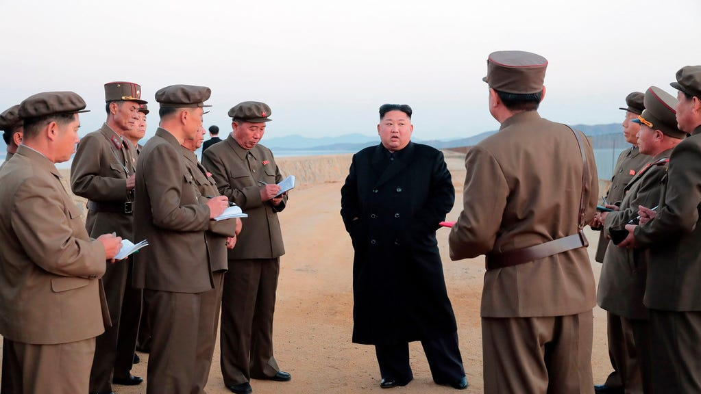 In this undated photo released Friday by the North Korean government, Kim Jong Un, center, listens to a military official as he inspects a weapon testing at the Academy of National Defense Science, North Korea.