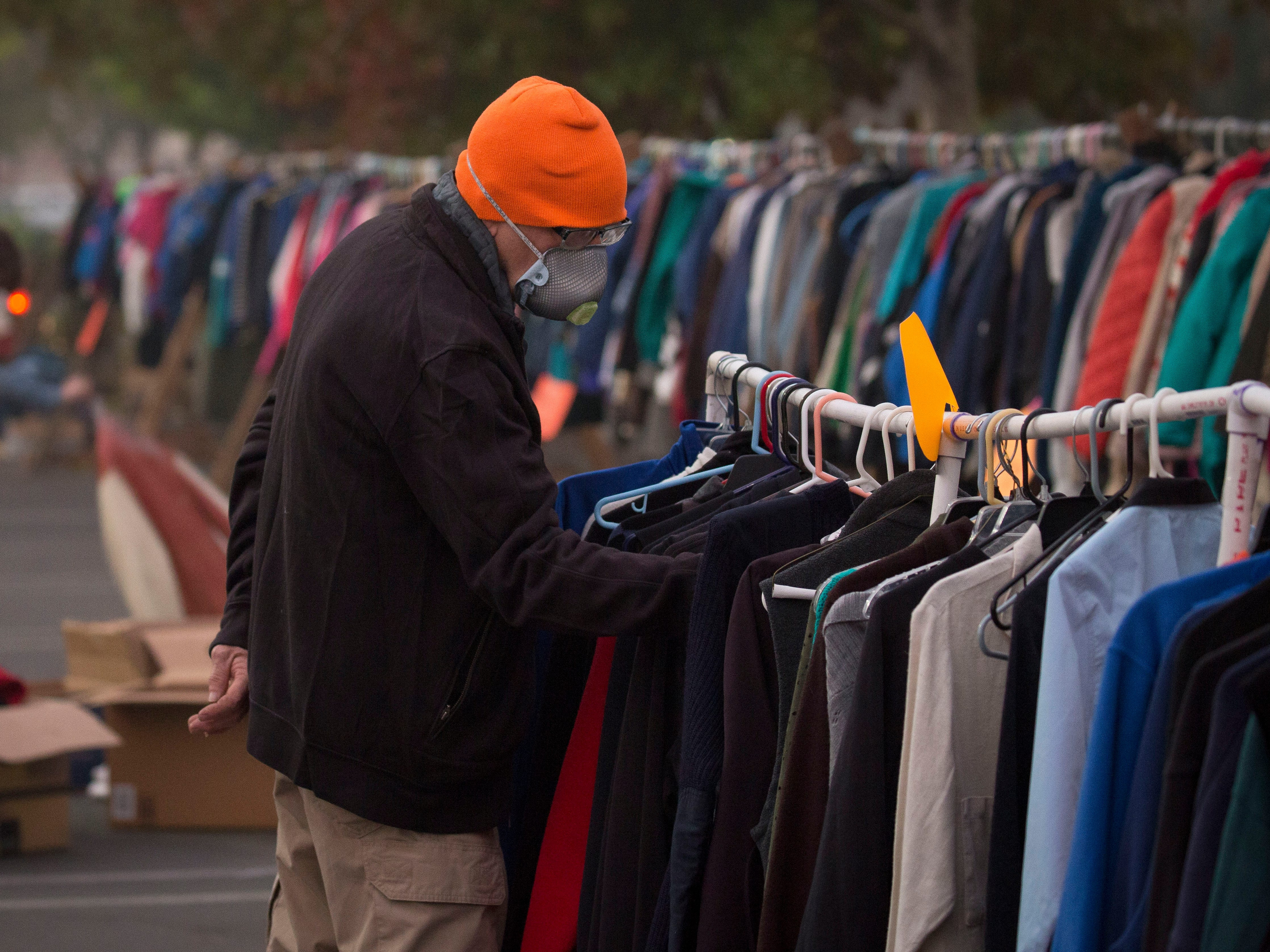 People look through clothing and other items in front of the old Toys 'R Us building where a make-shift camp has been set up to help fire victims of the Camp Fire.(Kelly Jordan / USA TODAY NETWORK) (Via OlyDrop)
