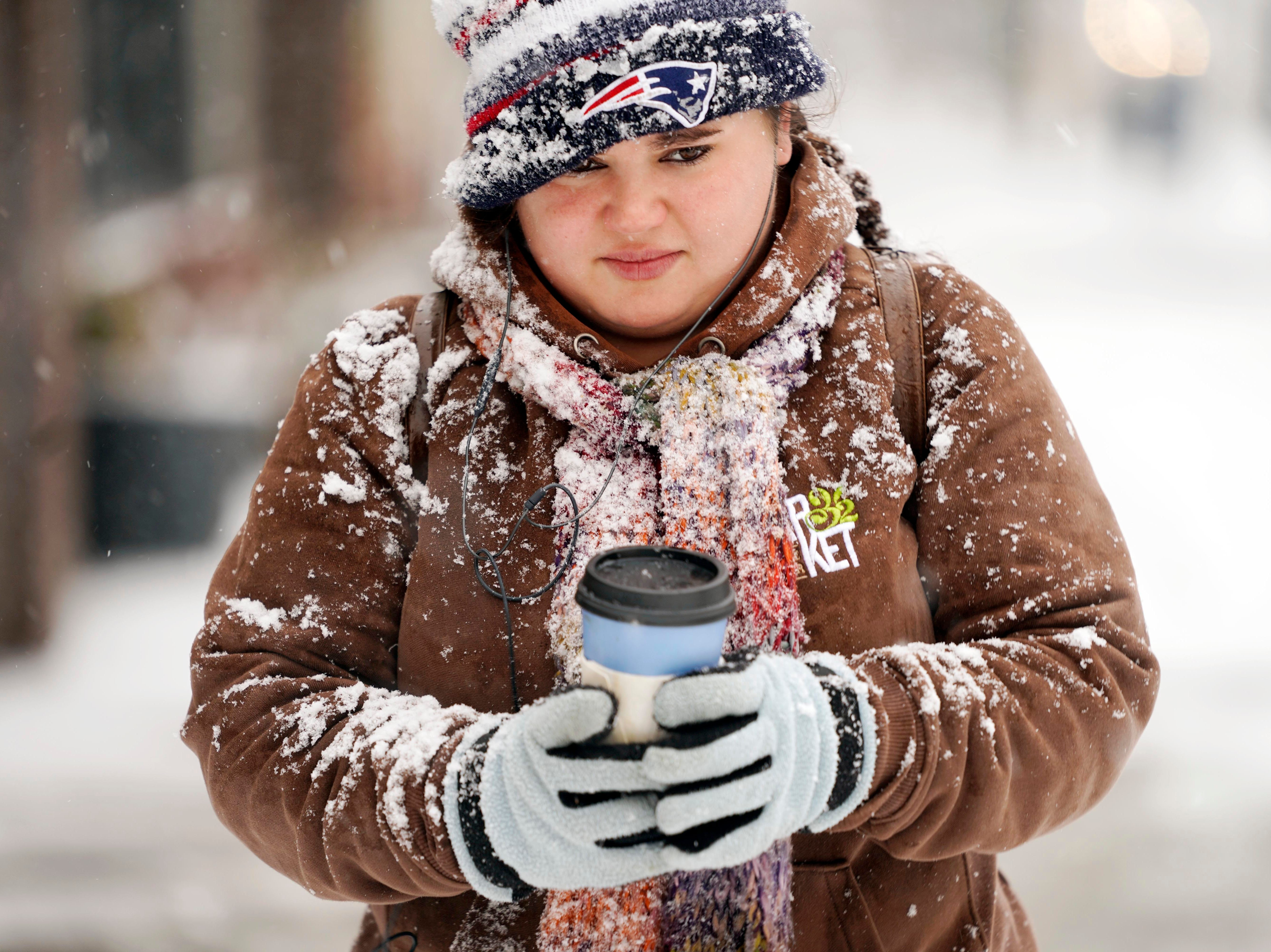 Jennifer Tanner holds a hot cup of coffee while walking in the snow, Friday, Nov. 16, 2018 in Pittsfield, Mass.