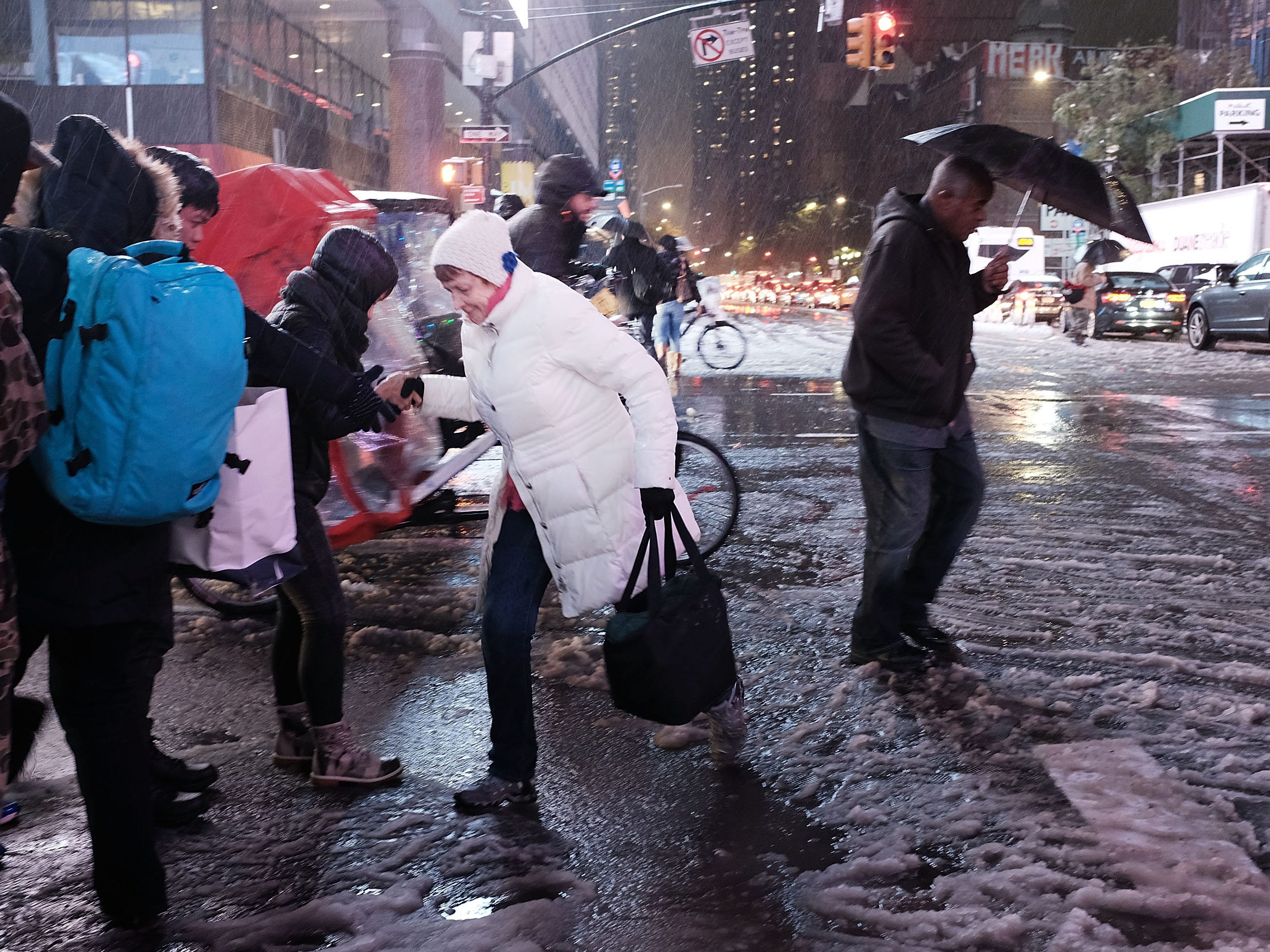 Pedestrians walk through a wintery mix of snow, rain and ice during the evening commute in Manhattan, Nov. 15, 2018 in New York City. New York experienced its first storm of the winter Thursday with over an inch of snow falling during the afternoon. A mix or rain and ice caused major backups along roadways and led to the cancellation of hundreds of buses.