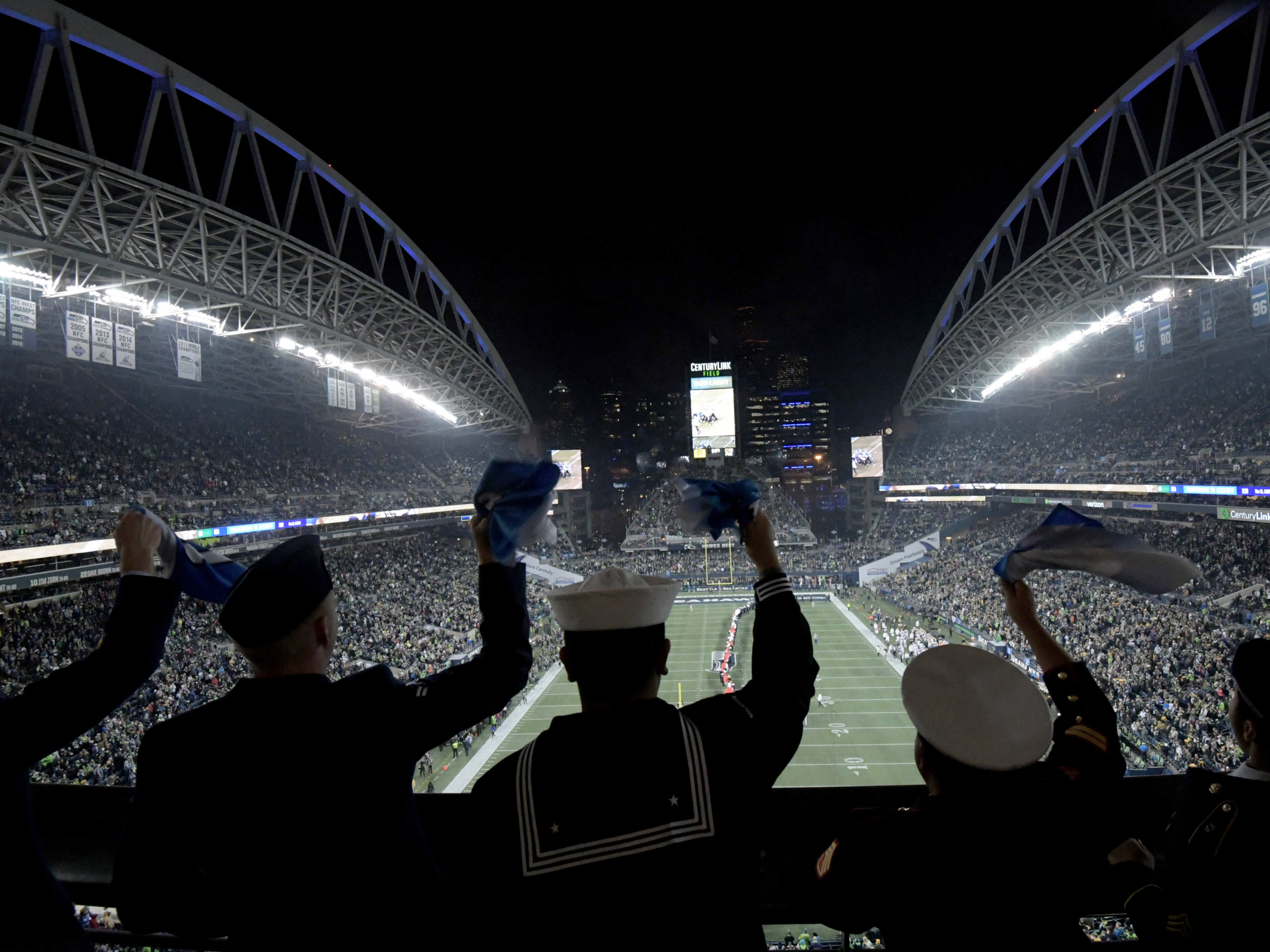 Military members are waving 12th man flags at CenturyLink Field before the national anthem prior to the game between the Green Bay Packers and Seattle Seahawks.