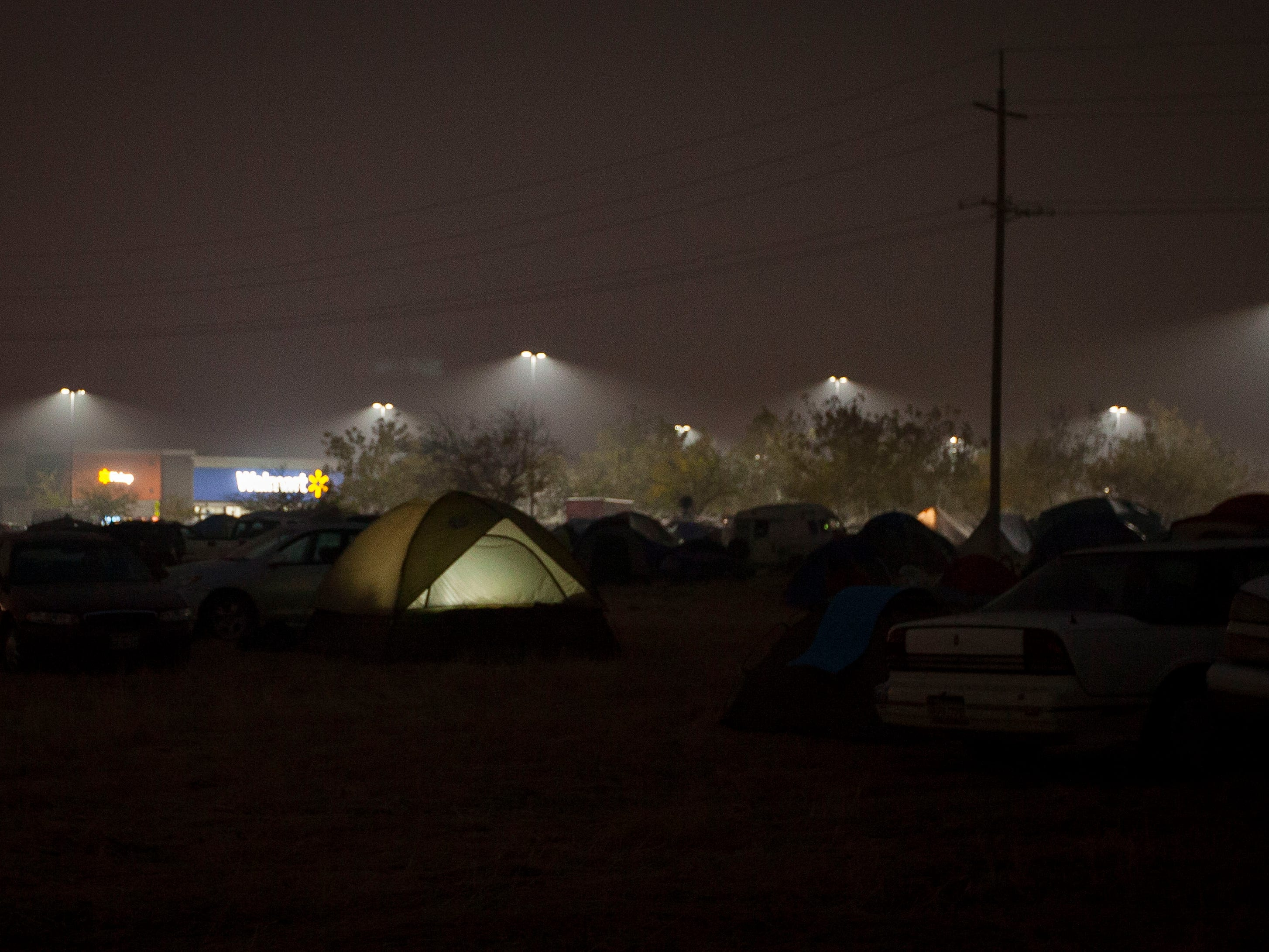 A tent glows from a light inside as people live in a make-shift tent compound next to the Walmart in Chico, Calif. Nov. 15, 2018. The parking lot and field next to it have become a refuge for evacuees of the Camp Fire which devastated Paradise. Officials are closing the area on Sunday and working to find a more sustainable housing solution for those affected by the fire.