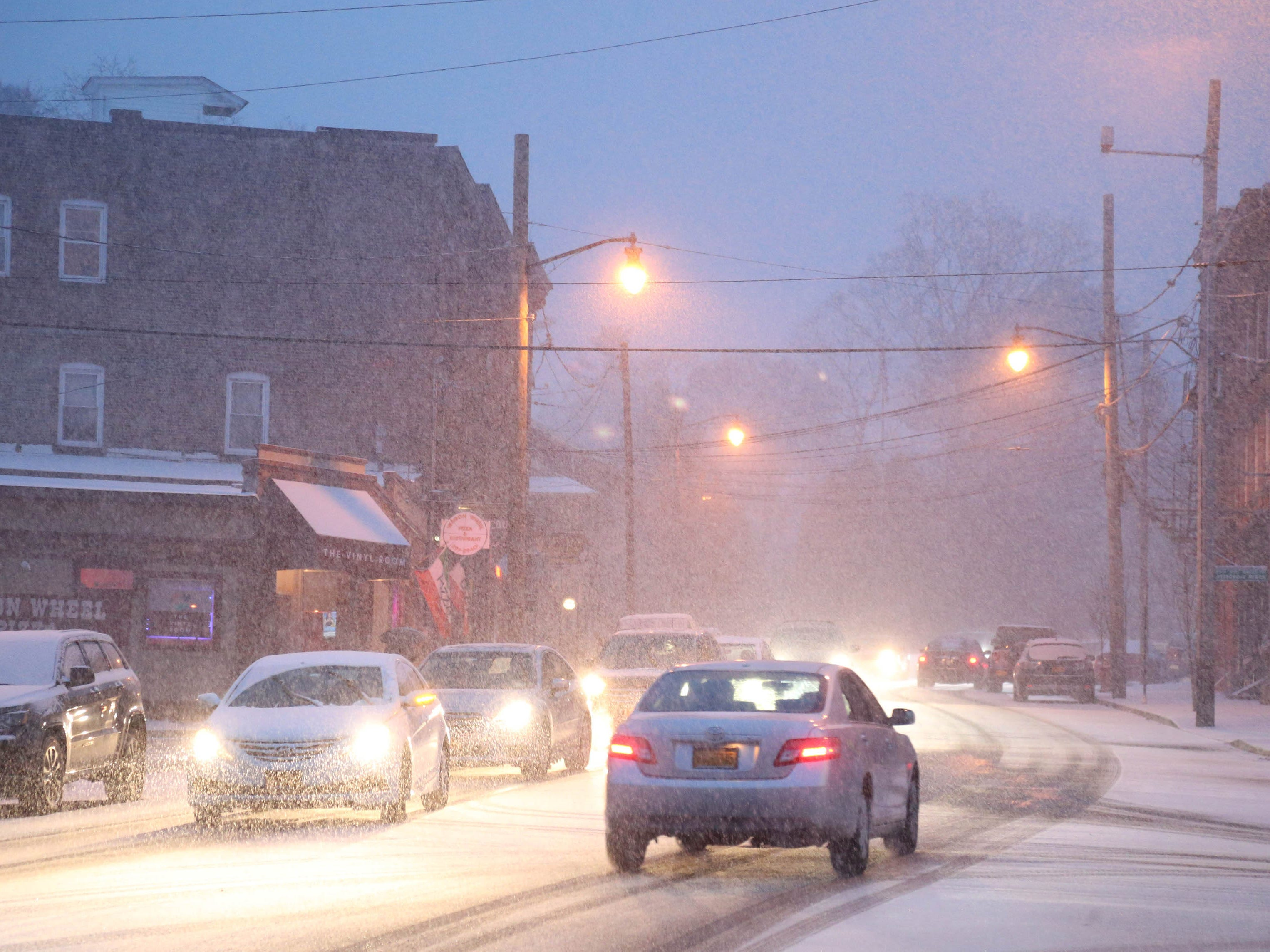 Traffic navigates its way along Main Street in the Village of Wappingers Falls, N.Y. as snow begins to accumulate on Nov. 15, 2018.