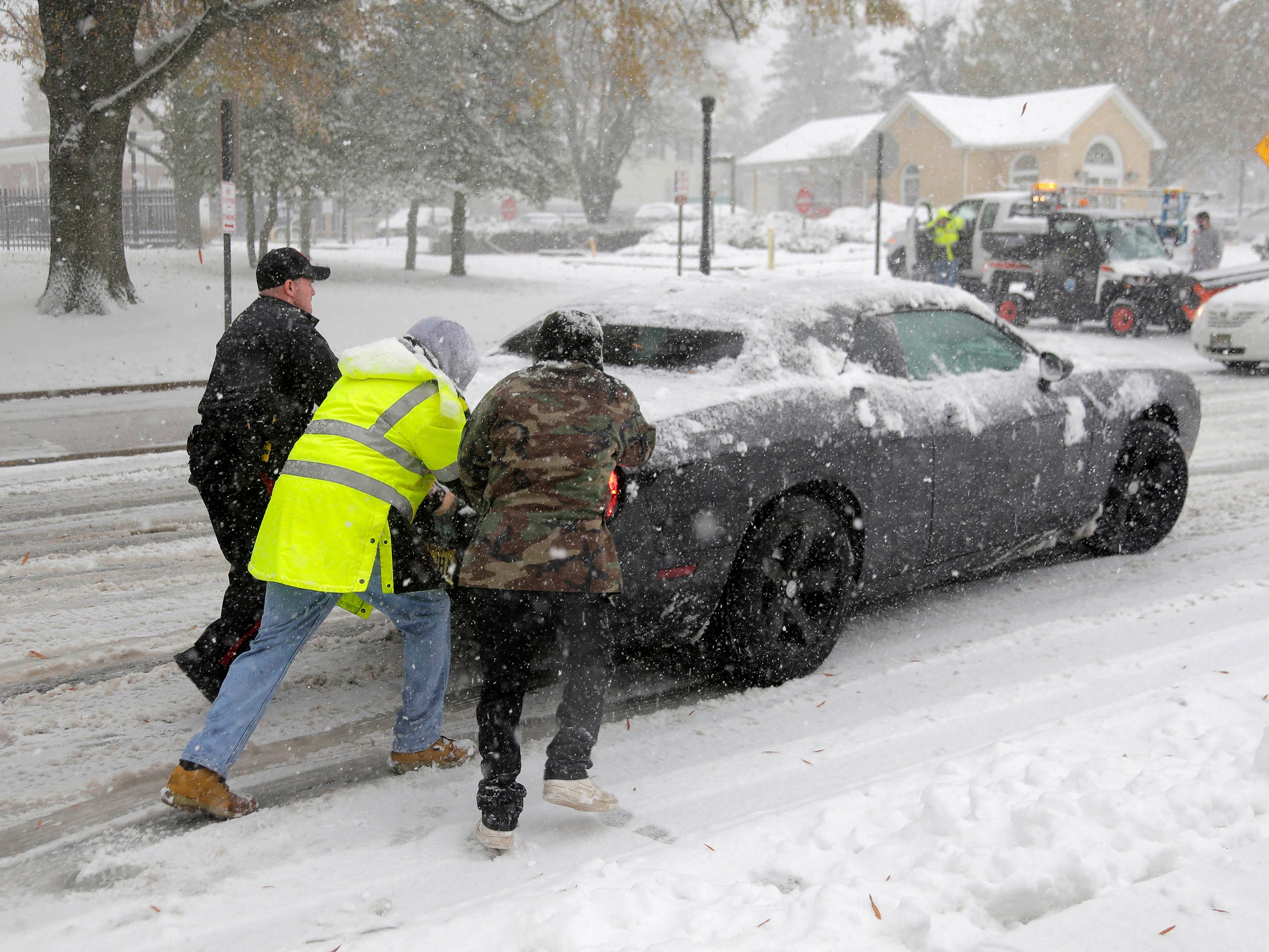A police officer and others help push a car that was unable to gain traction on the snowy roads in Mt. Holly, N.J. on Nov. 15, 2018.