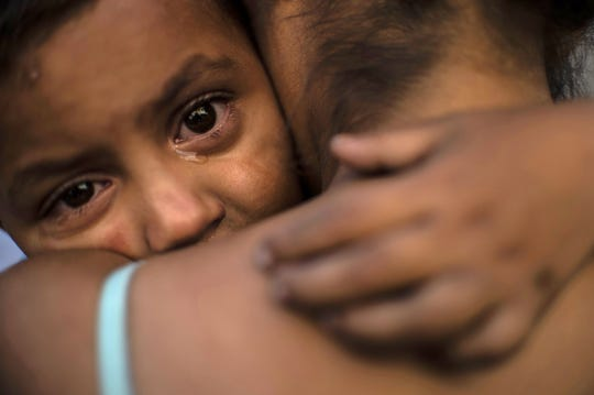A Central American migrant child moving with a caravan towards the United States in hopes of a better life, cries as she embraces a woman at the Alfa y Omega shelter in Mexicali, Baja California state, Mexico, on Nov. 16, 2018.  The Central American migrant caravan trekking toward the United States converged on the US-Mexican border Thursday after more than a month on the road, undeterred by President Donald Trump's deployment of thousands of American troops near the border.
