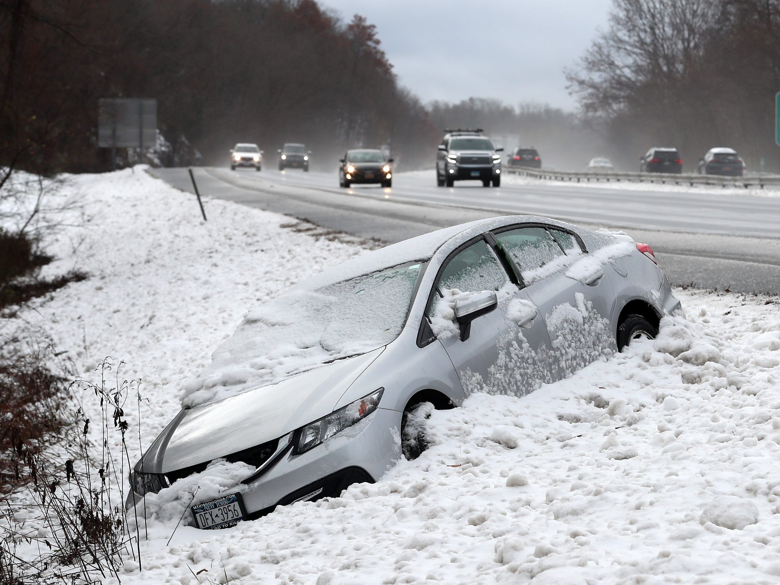 Northbound traffic passes by as a car that went off  Interstate 684 at the Goldens Bridge exit during last nights snowstorm waits to be towed on Nov. 16, 2018.