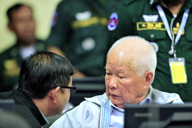 This handout photo taken and released by the Extraordinary Chambers in the Courts of Cambodia (ECCC) on November 16, 2018 shows former Khmer Rouge leader head of state Khieu Samphan listens to his lawyer in court at the ECCC in Phnom Penh. - Two senior Khmer Rouge leaders were sentenced to life imprisonment for genocide for their part in the regime's 1975-1979 reign of terror, a UN-backed war crimes court said on November 16 in a historic ruling.