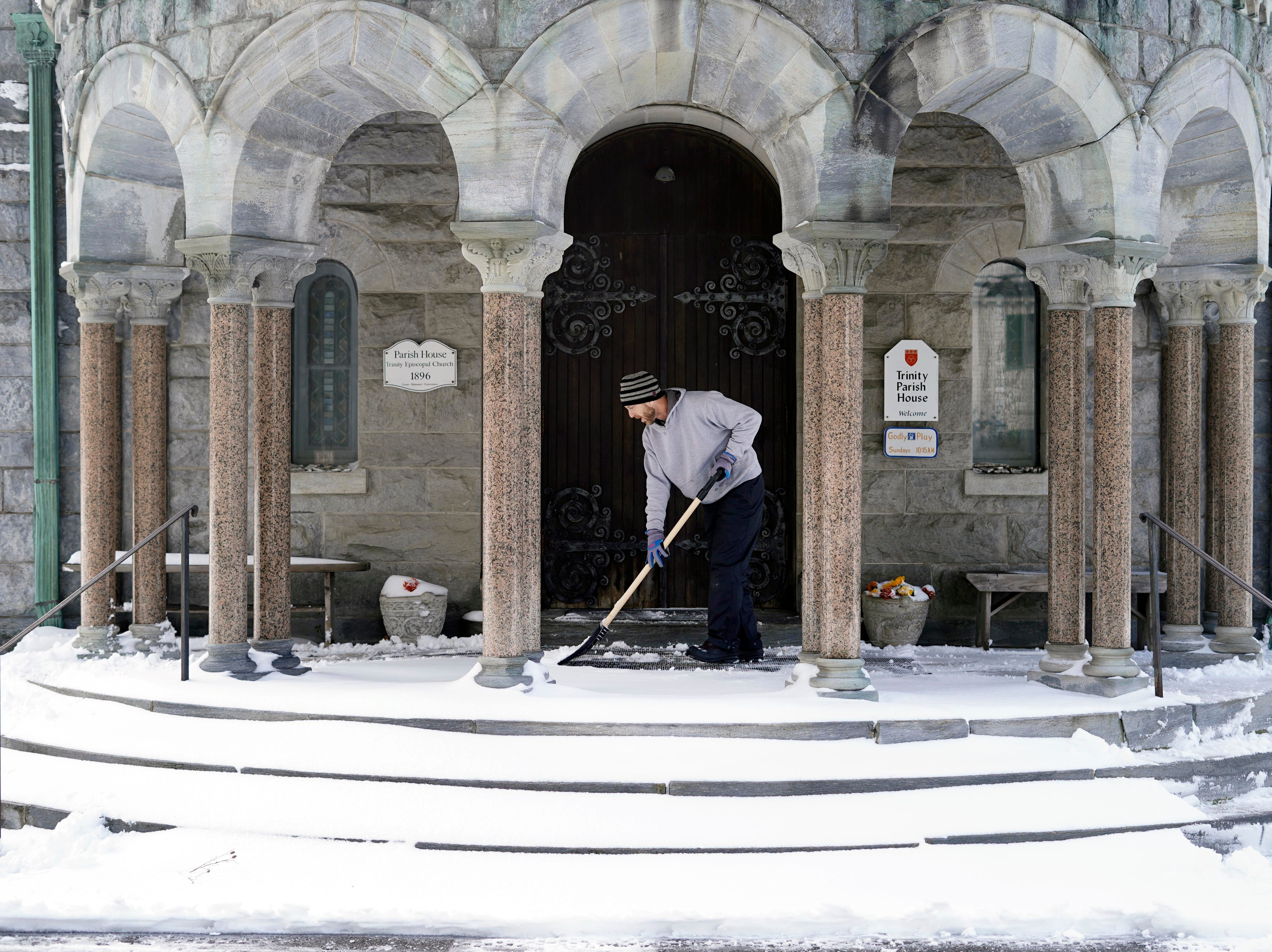 Chris Brown clears snow from the entrance of the Trinity Parish House in Lenox, Mass., Friday, Nov. 16, 2018. The first snowstorm of the season caused minor delays in Western Massachusetts.