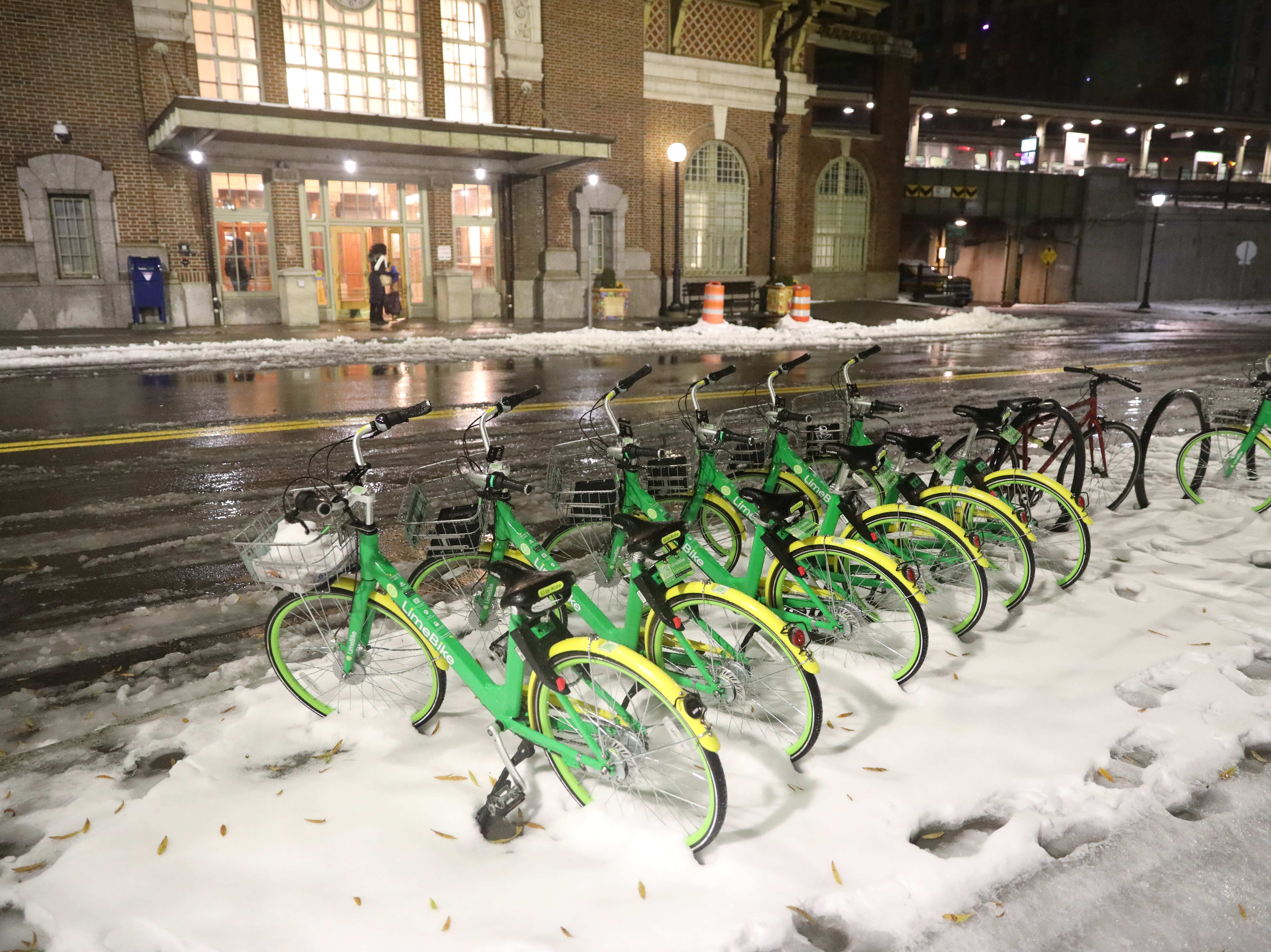 Lime Bikes sit in snow in front of the Yonkers Train Station in Yonkers, Nov. 16, 2018.