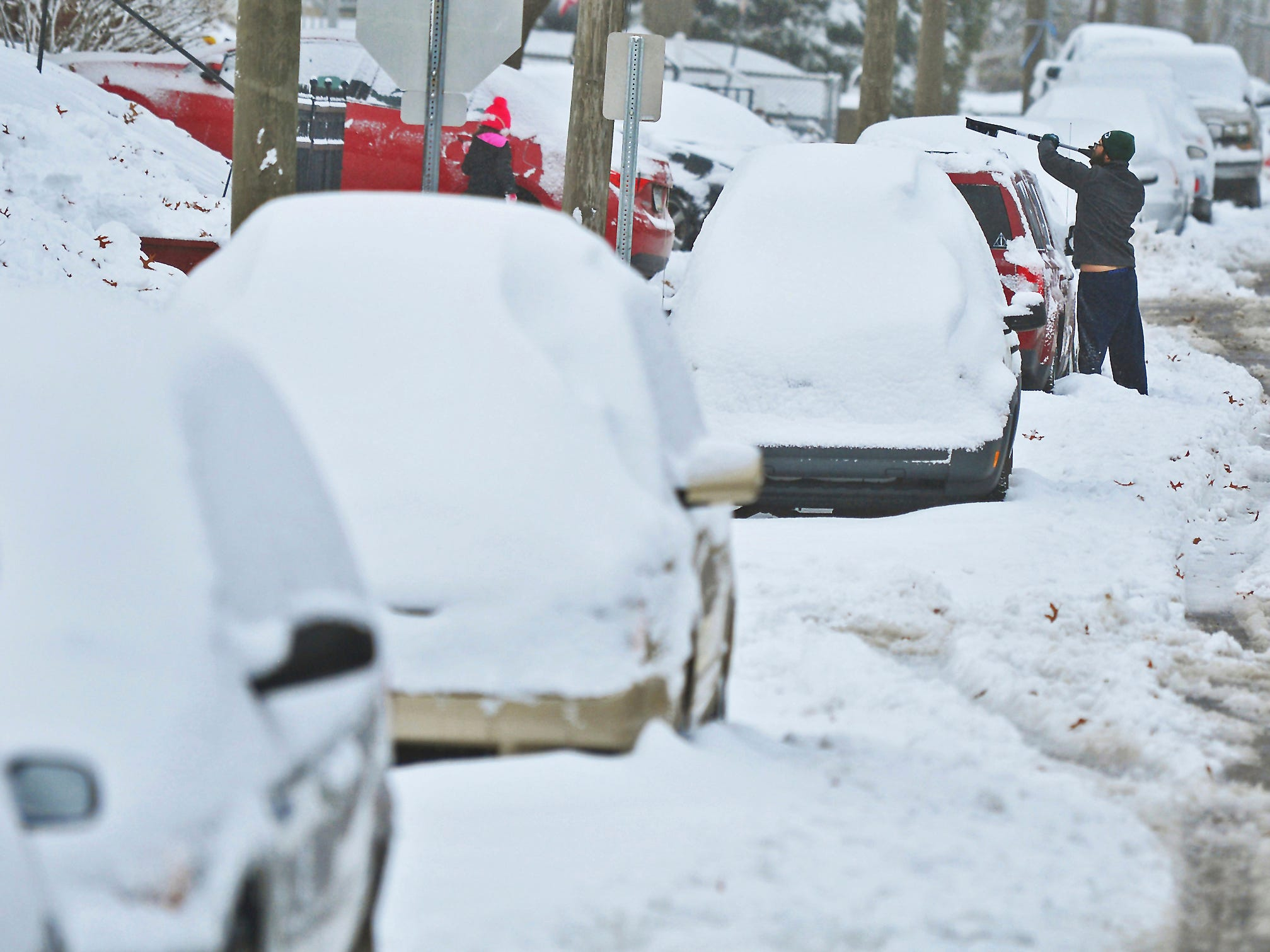 A resident clears away snow from a vehicle in Blakely, Pa., on Friday, Nov. 16, 2018. The first snowstorm of the season caused havoc around Pennsylvania, downing trees and power lines and causing a travel nightmare, including for some drivers who were stuck for 12 hours on a snowy interstate.