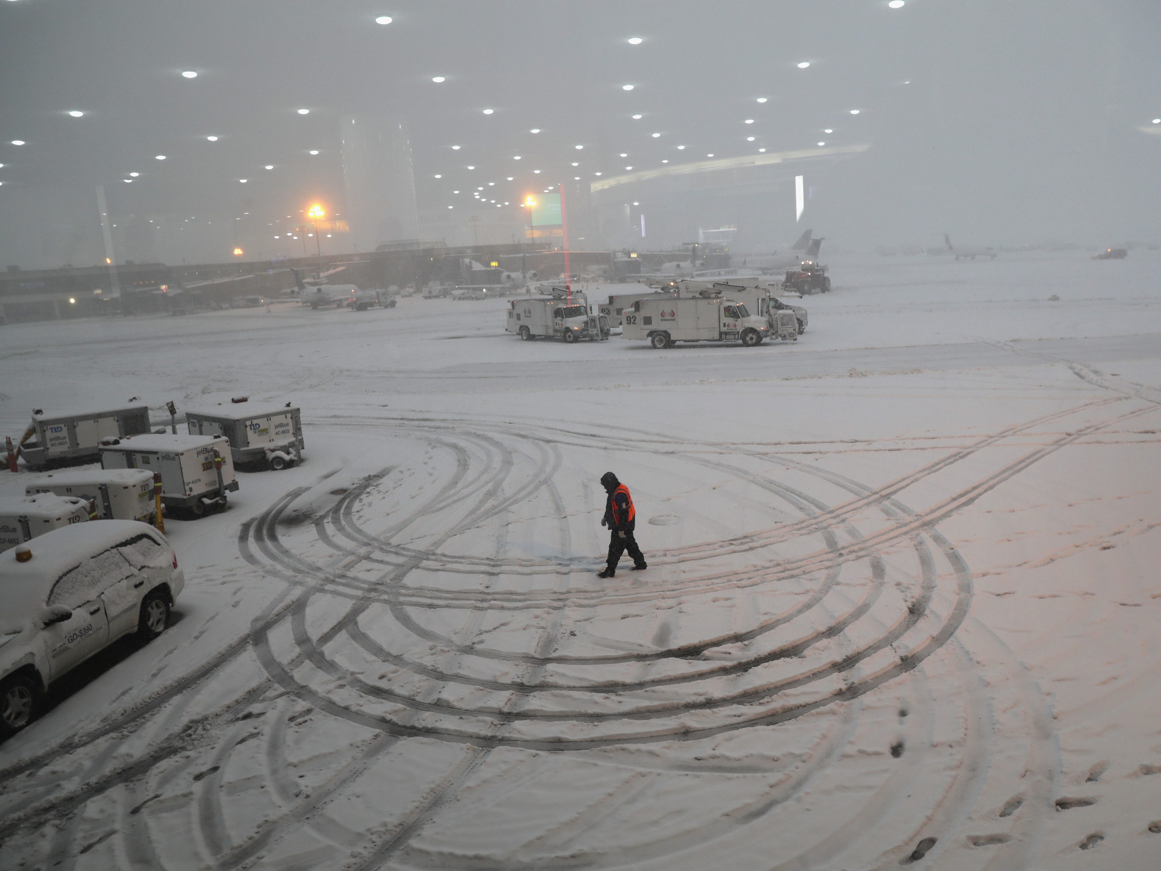 A ground crew member walks through the snow at the Newark Liberty International Airport on Nov. 15, 2018 in Newark, New Jersey.