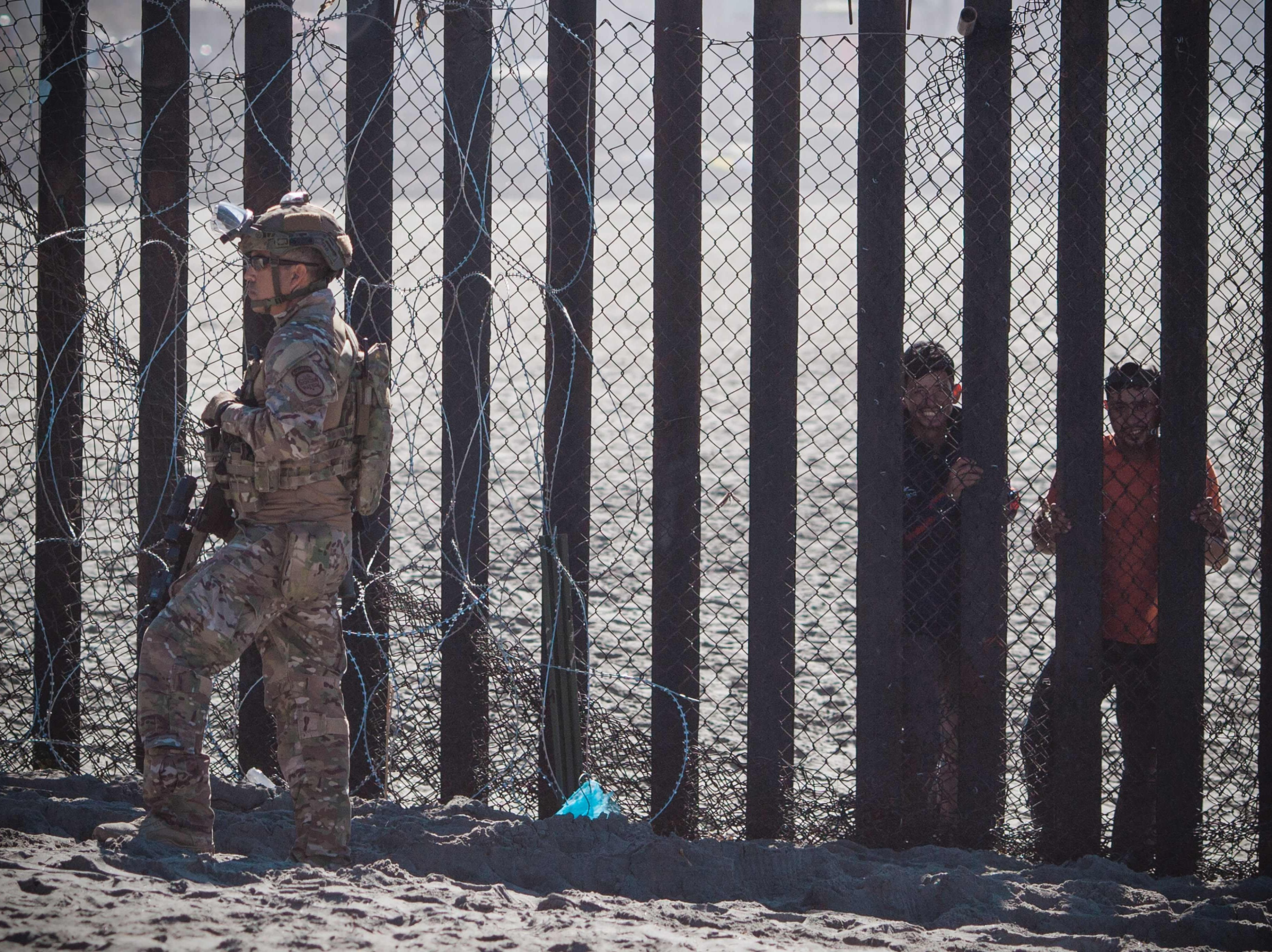 A member of the US military stands in front of the border fence that divides the US and Mexico at Friendship Park on Nov. 16, 2018 in San Diego, Calif.