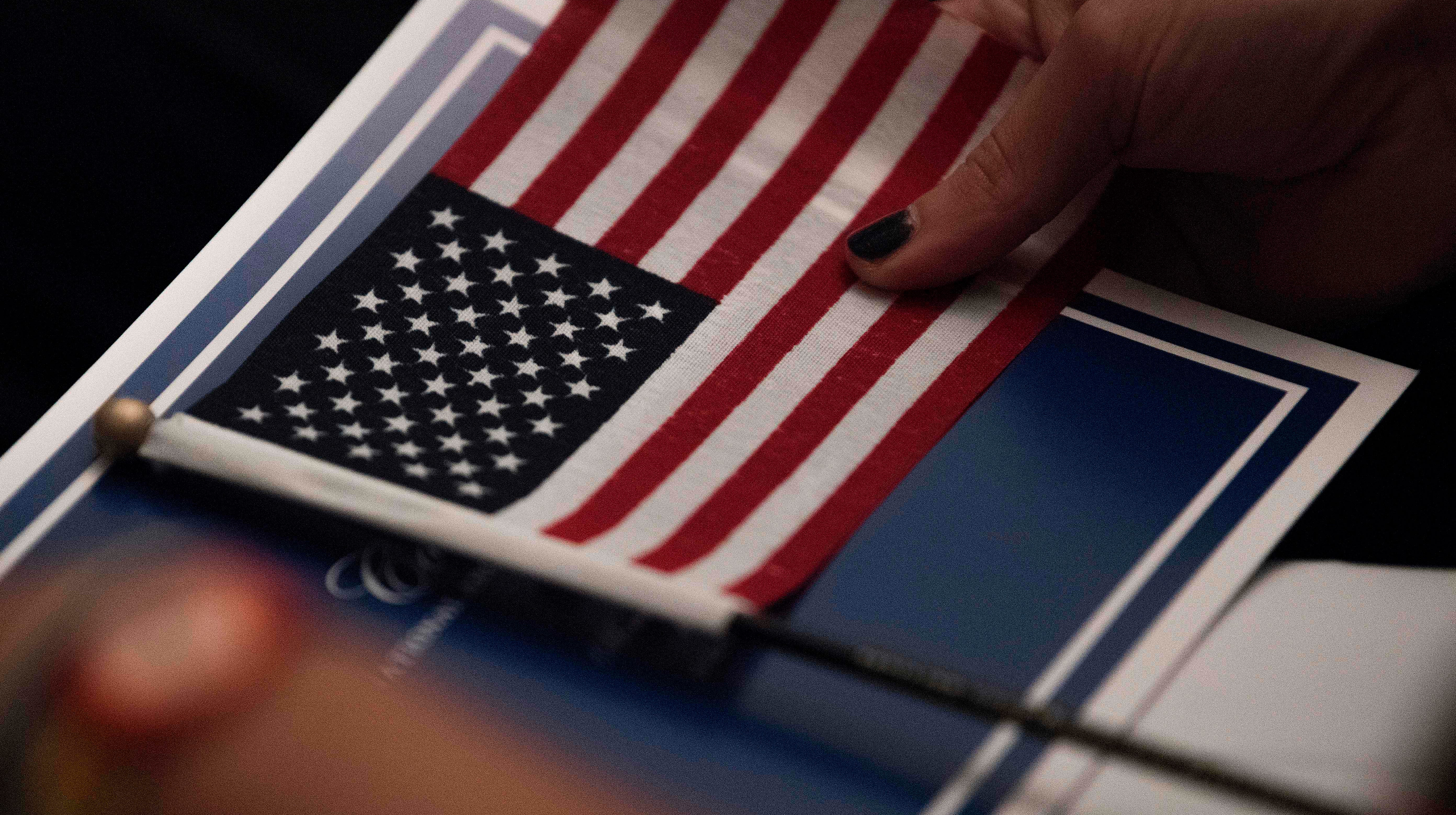 A woman holds an American flag during a naturalization ceremony at the National Archives in Washington, D.C.