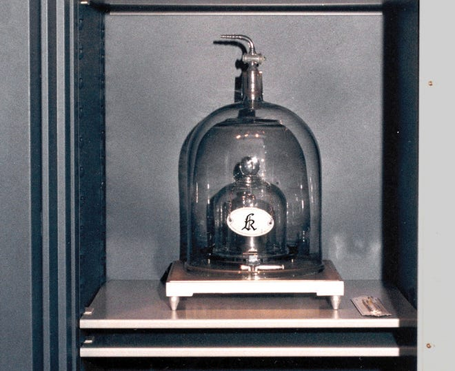 """A handout photo dated 2001, made available by the International Bureau of Weights and Measures, shows the international prototype of the kilogram (aka """"Grand K""""), a cylinder of platinum and iridium, which is the official definition of the kilogram, and its official copies in a safe in Sevres, near Paris."""