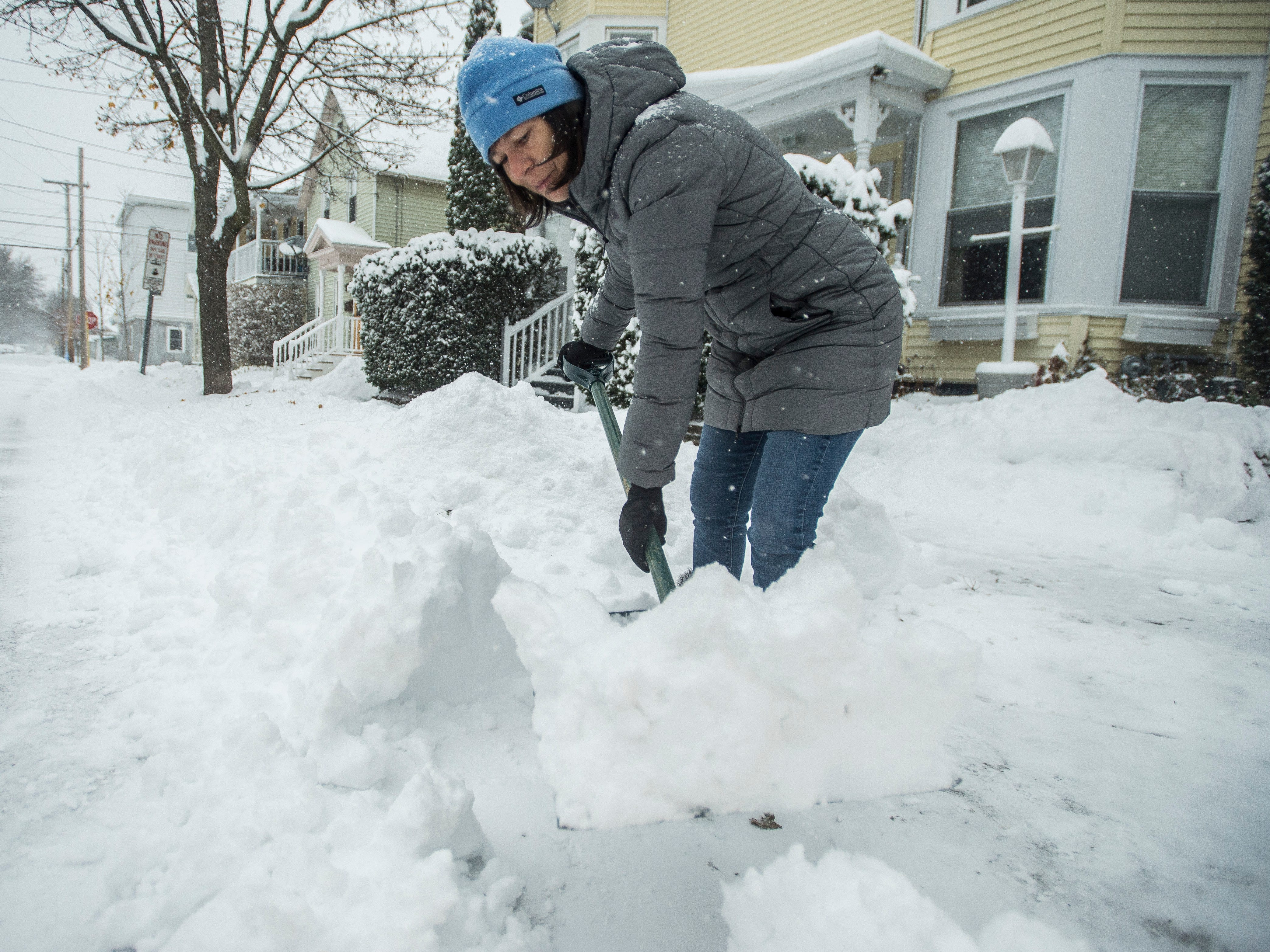 Charmaine Vincent shovels out her driveway in Burlington, Vt.  Nov. 16, 2018, as a winter storm moved into Vermont, promising up to a foot of snow or more in some areas.